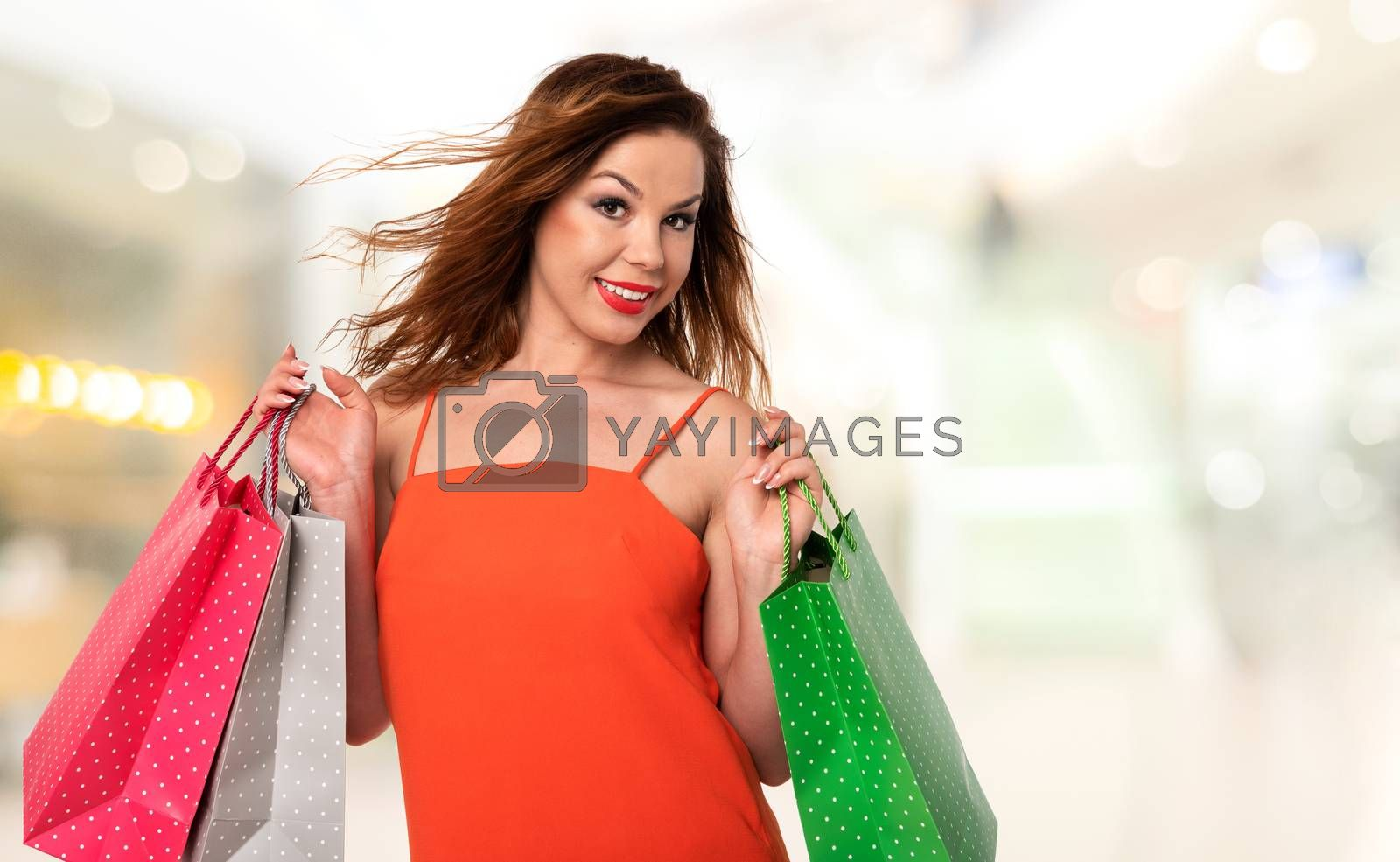 Attractive and young woman holds bags in her hands and enjoys shopping on a background of blurred mall (copy space).