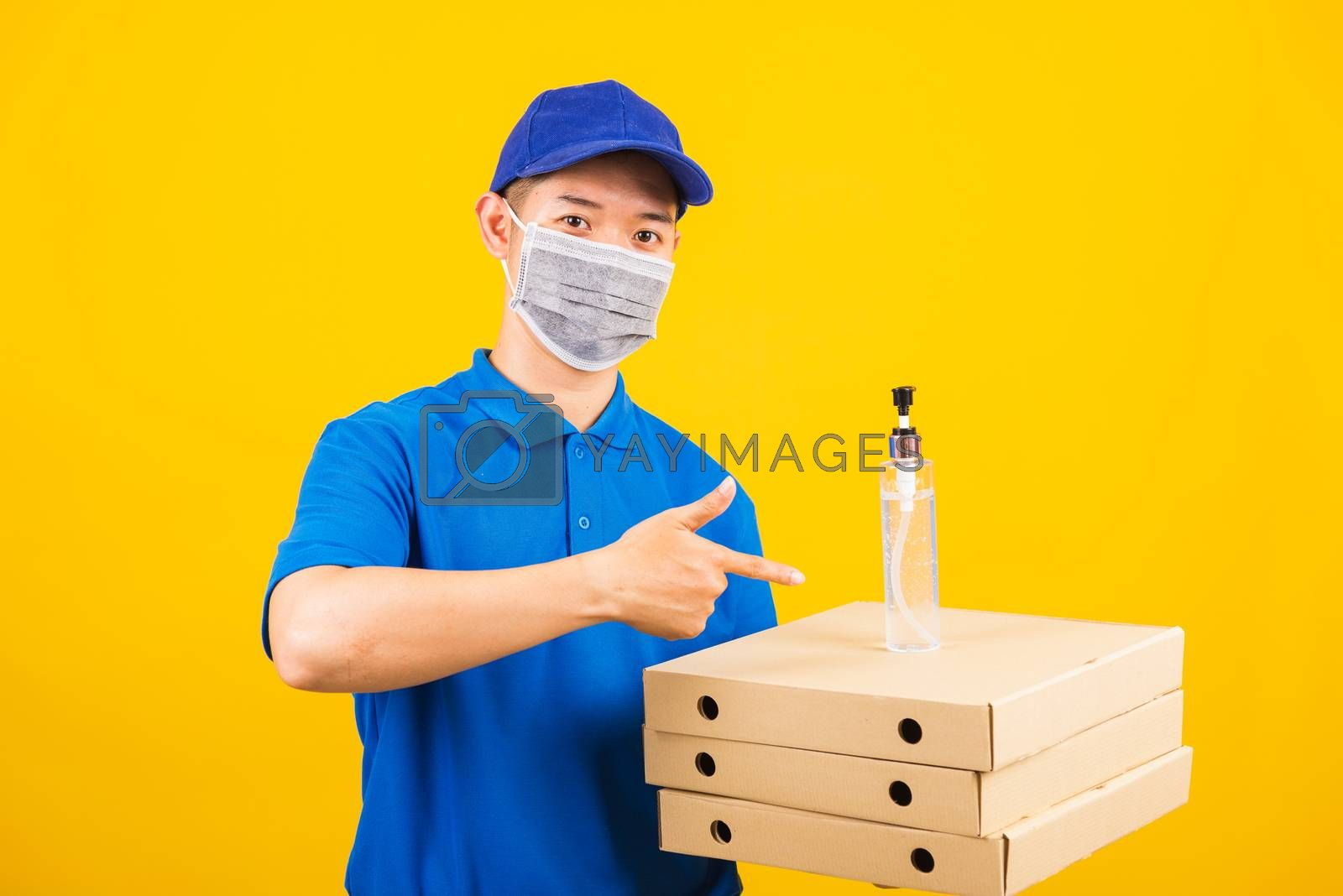 Asian young handsome delivery man wearing face mask protective germ virus holding boxes on hand and point alcohol sanitizing gel, studio shot isolated yellow background, outbreak coronavirus COVID-19