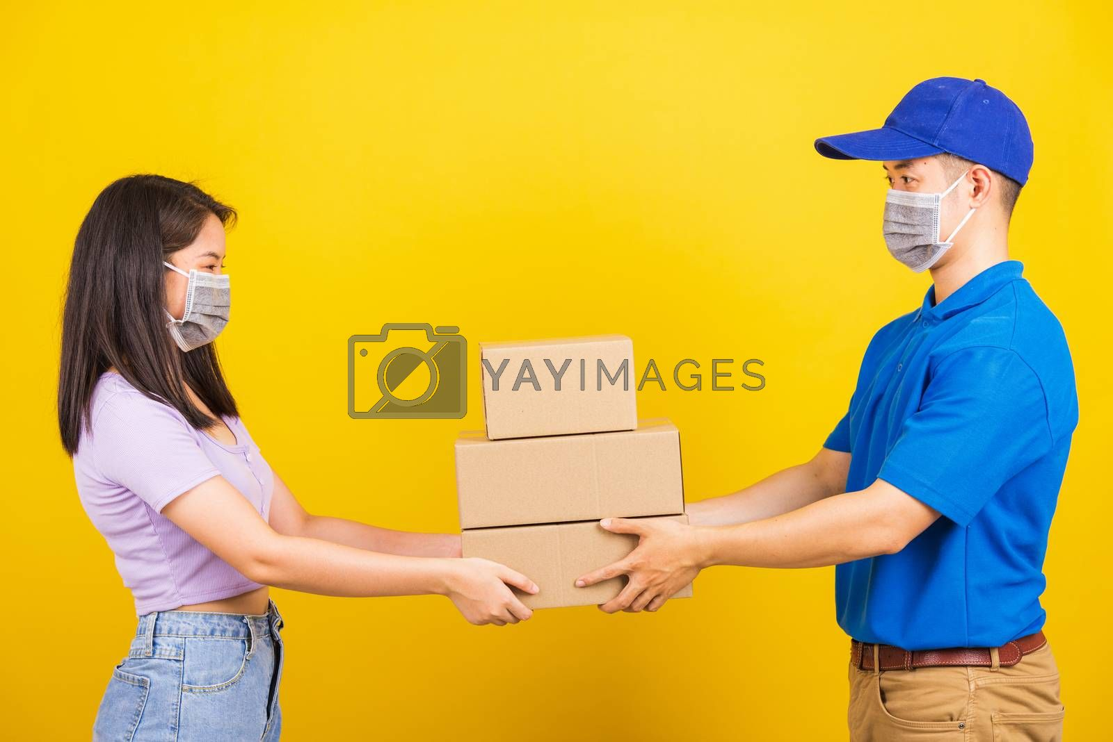 Asian beautiful woman and handsome man wearing protection face mask against coronavirus, accepting delivery boxes, studio shot isolated on yellow background, COVID-19 or corona virus concept