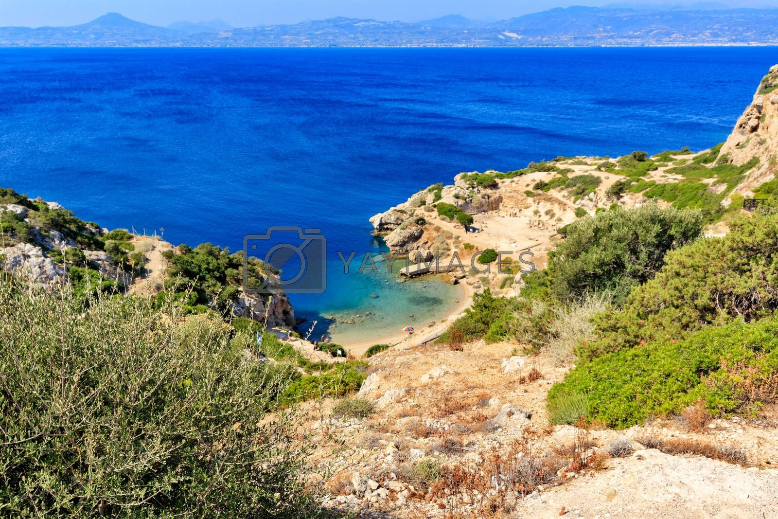 Rigid shrubbery grows on the rocky slopes of the Greek Corinthian Gulf on the background of a blue lagoon on the coast, a beautiful view from above, image with copy space.