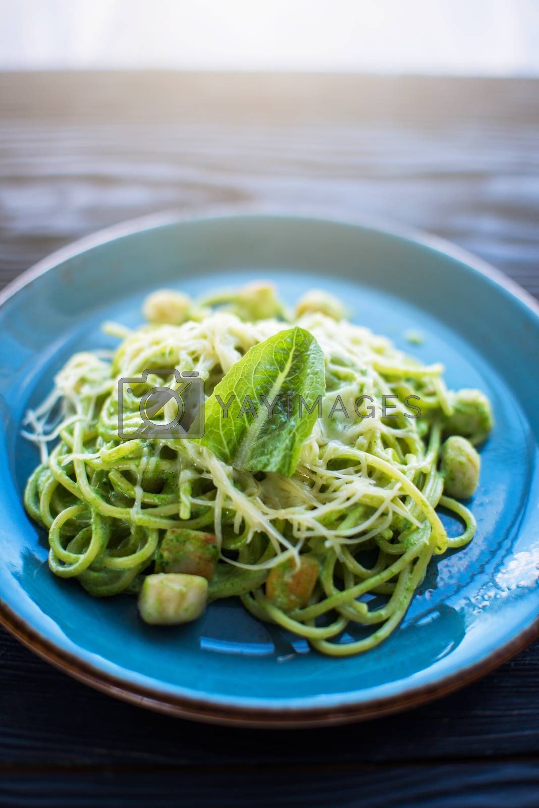 Green Pasta with scallop and sauce on blue plate