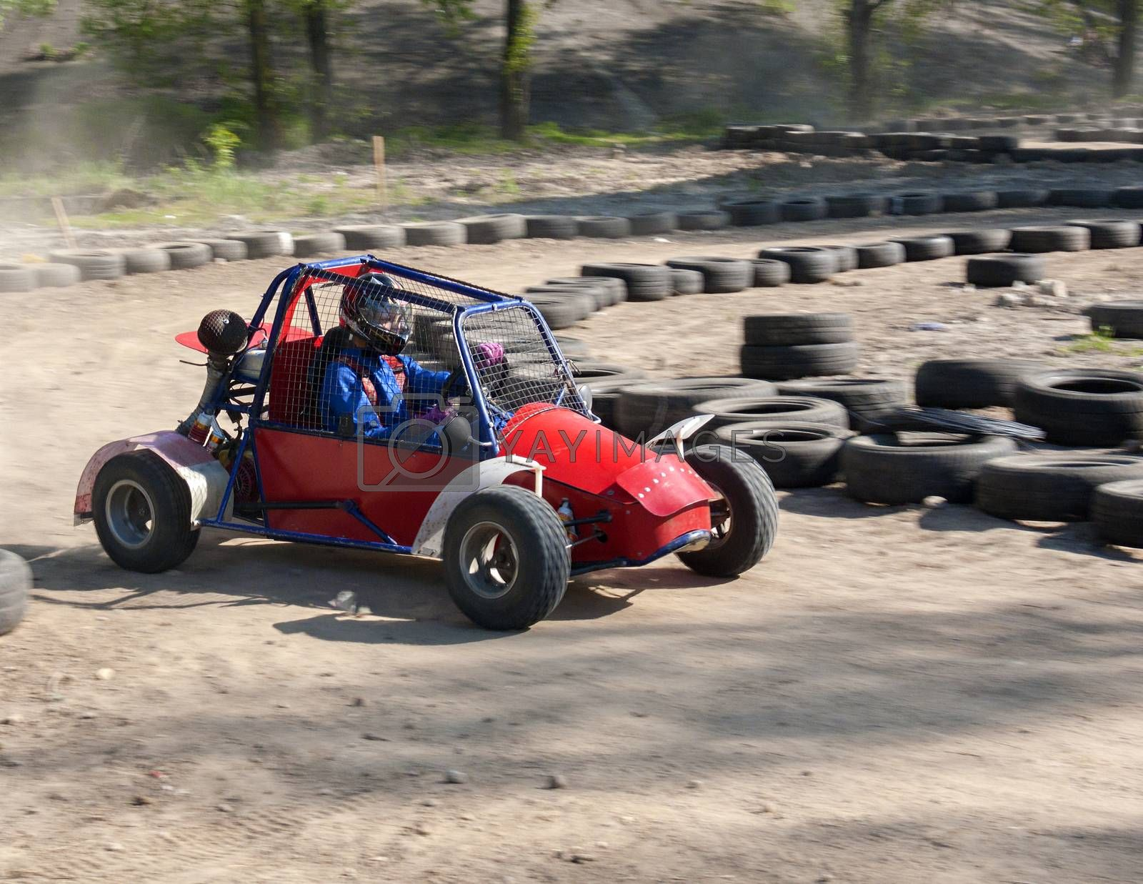 Race of a teenager on a children's buggy kicking up trail of dust on sand track