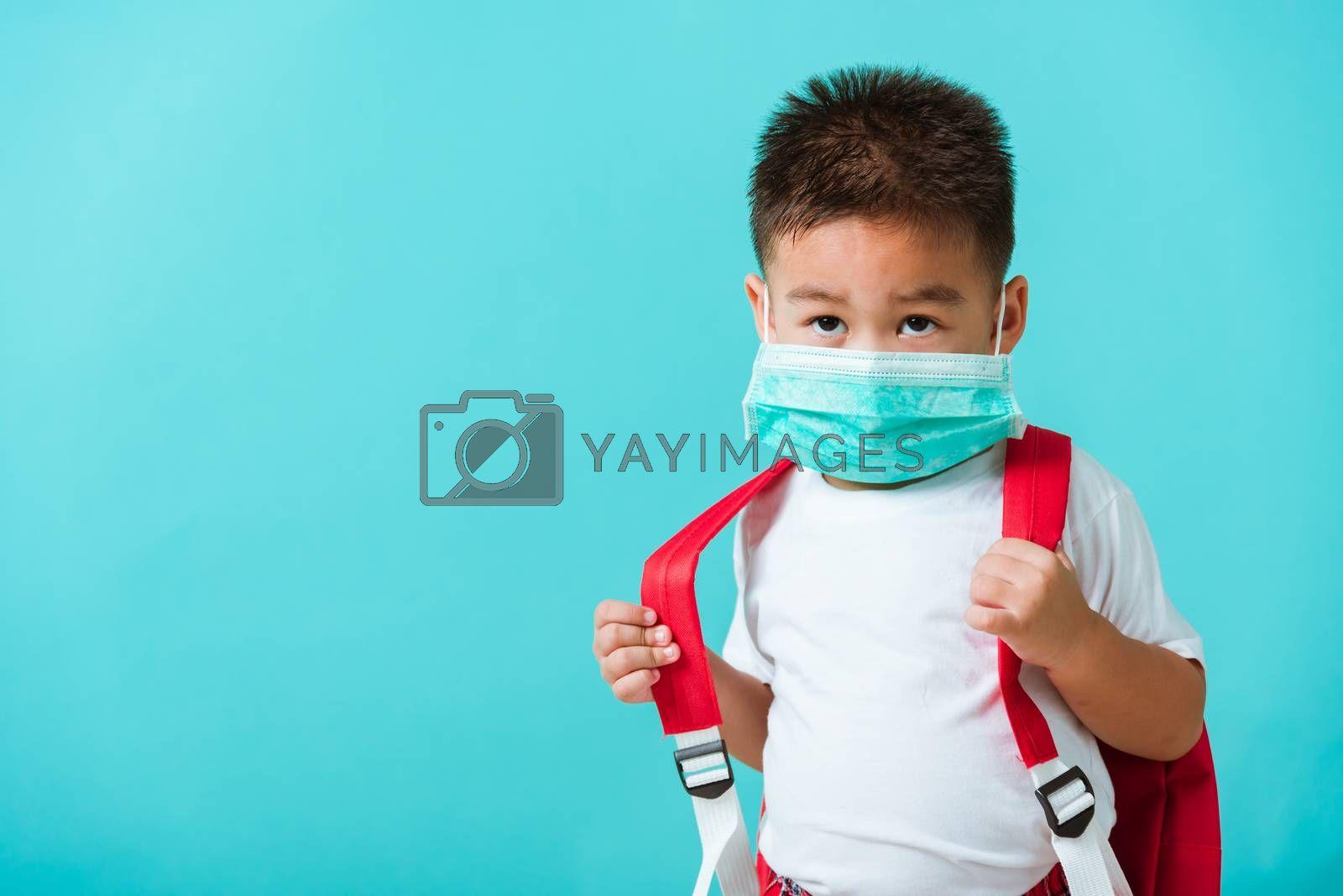 Back to school coronavirus Covid-19 education. Portrait Asian cute little child boy kindergarten wear face mask protective and school bag before going to school, studio shot isolated blue background