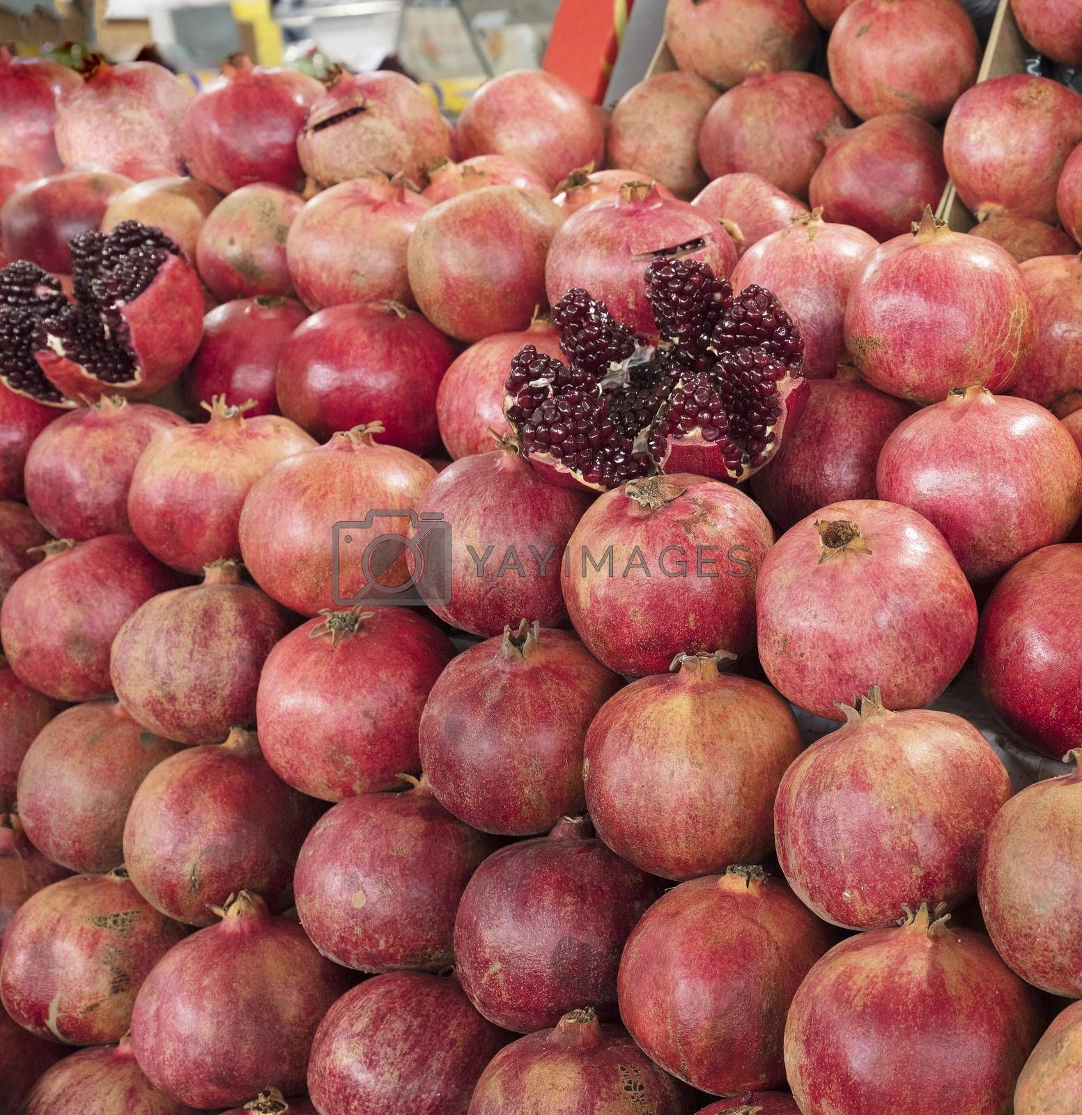 Ripe and red fruit pomegranate and divided into four parts, against the background of pomegranate fruit lined in rows
