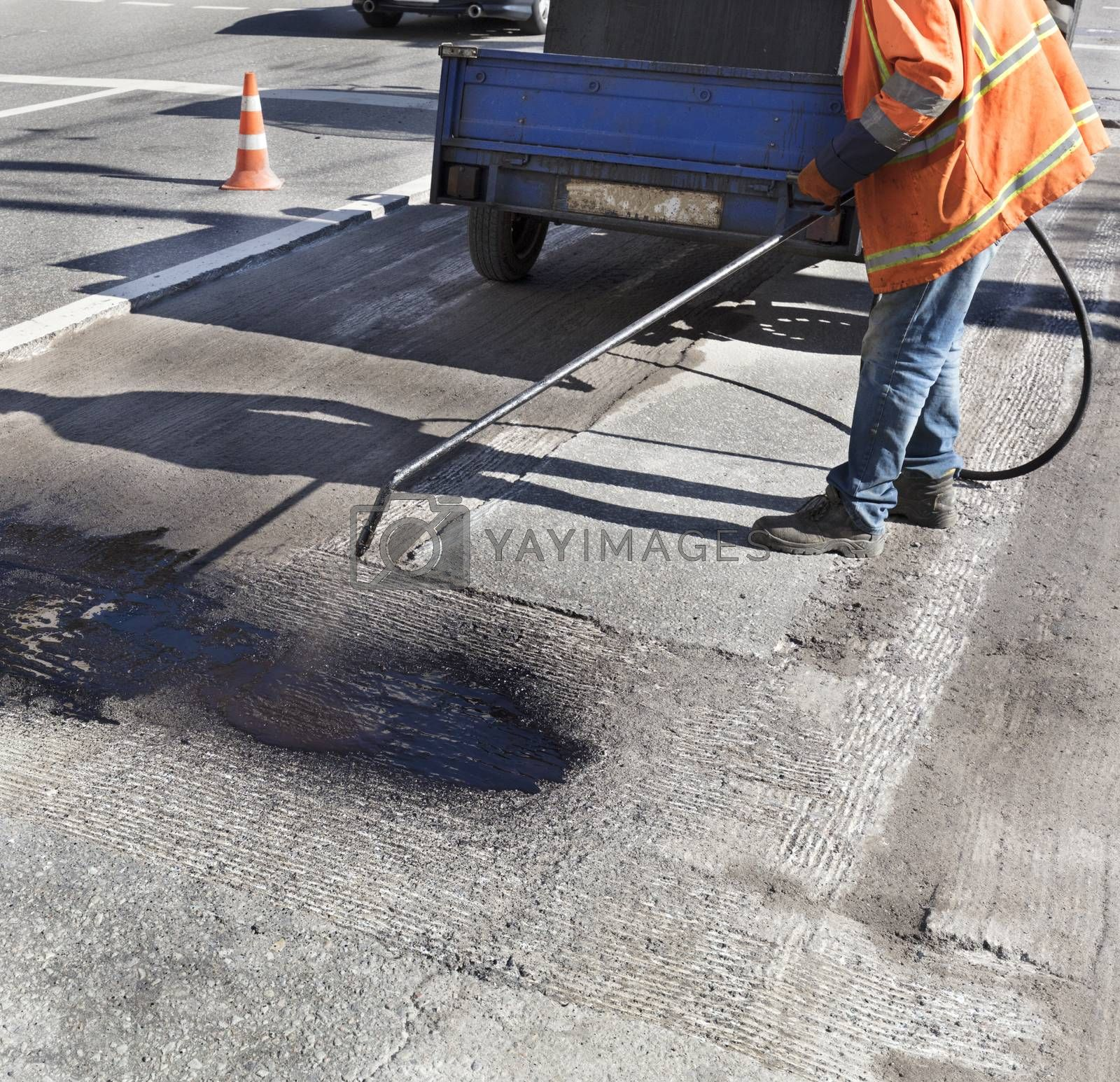The road maintenance worker sprays the bitumen mixture onto the cleaned area for better adhesion to the new asphalt