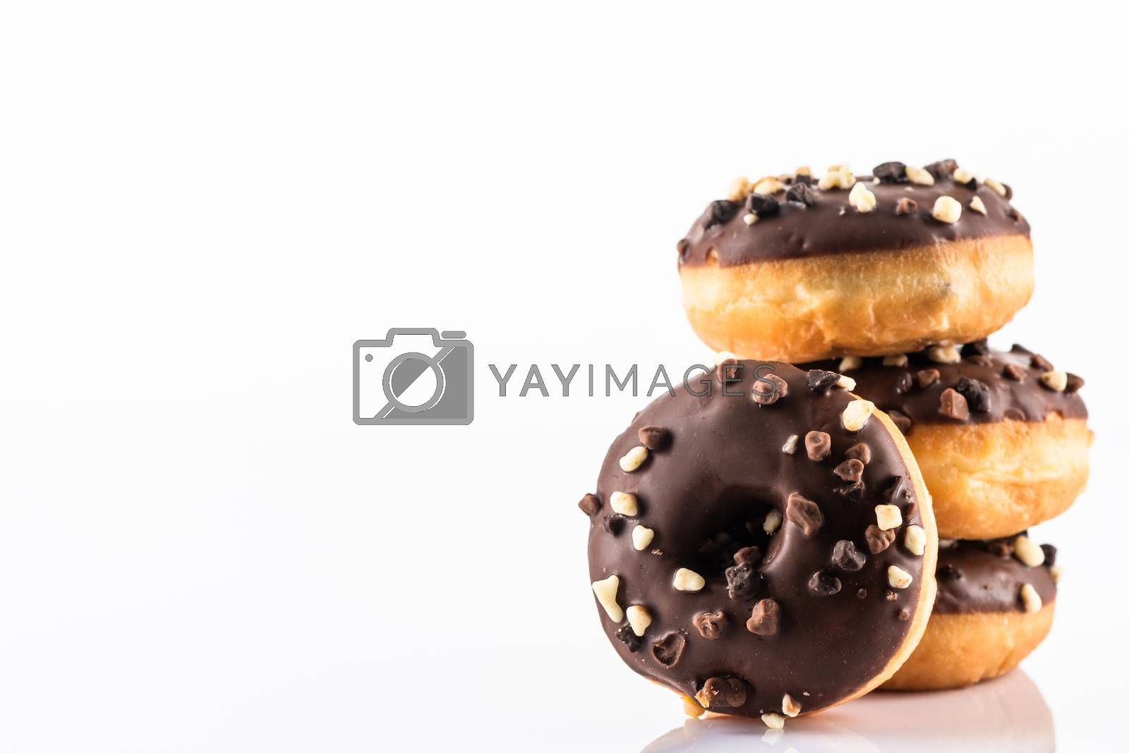 Chocolate Donut or Doughnuts on White Reflective Background with Copy Space.