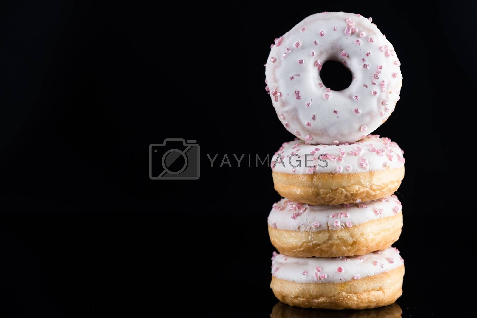 White Chocolate Donuts or Doughnuts Tower on Dark Background. Copy Space for Text.