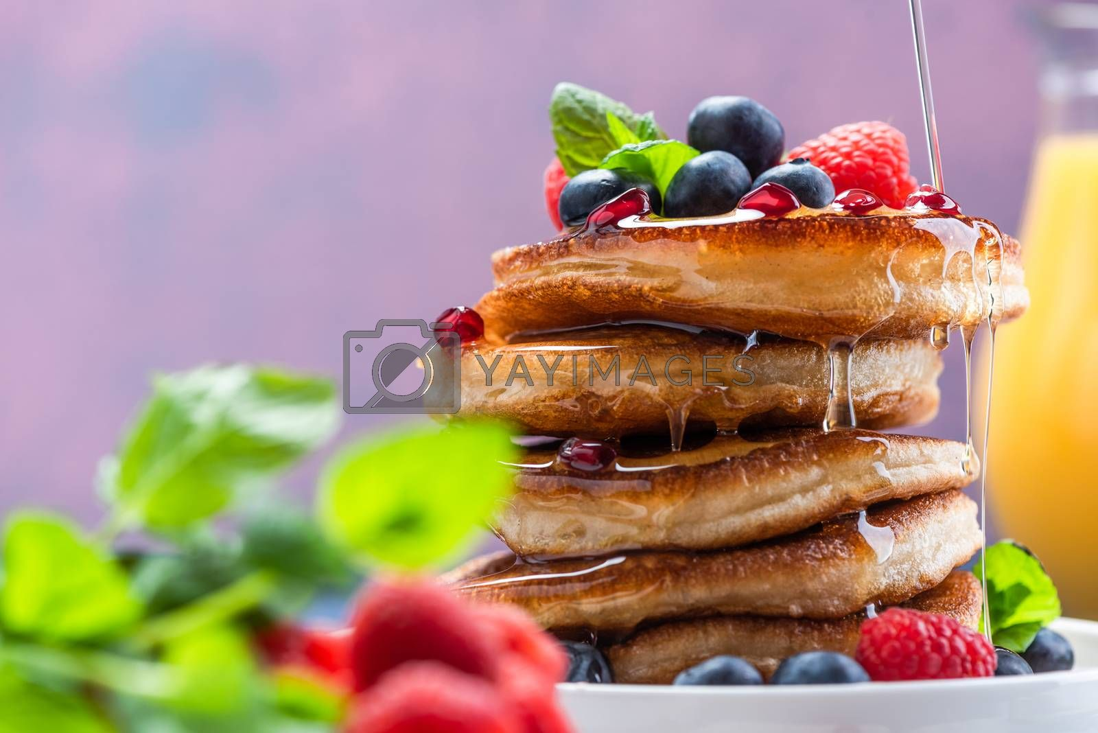 Pouring Maple Syrup on American Pancakes Topped with Fresh Fruits. Shrove Tuesday.