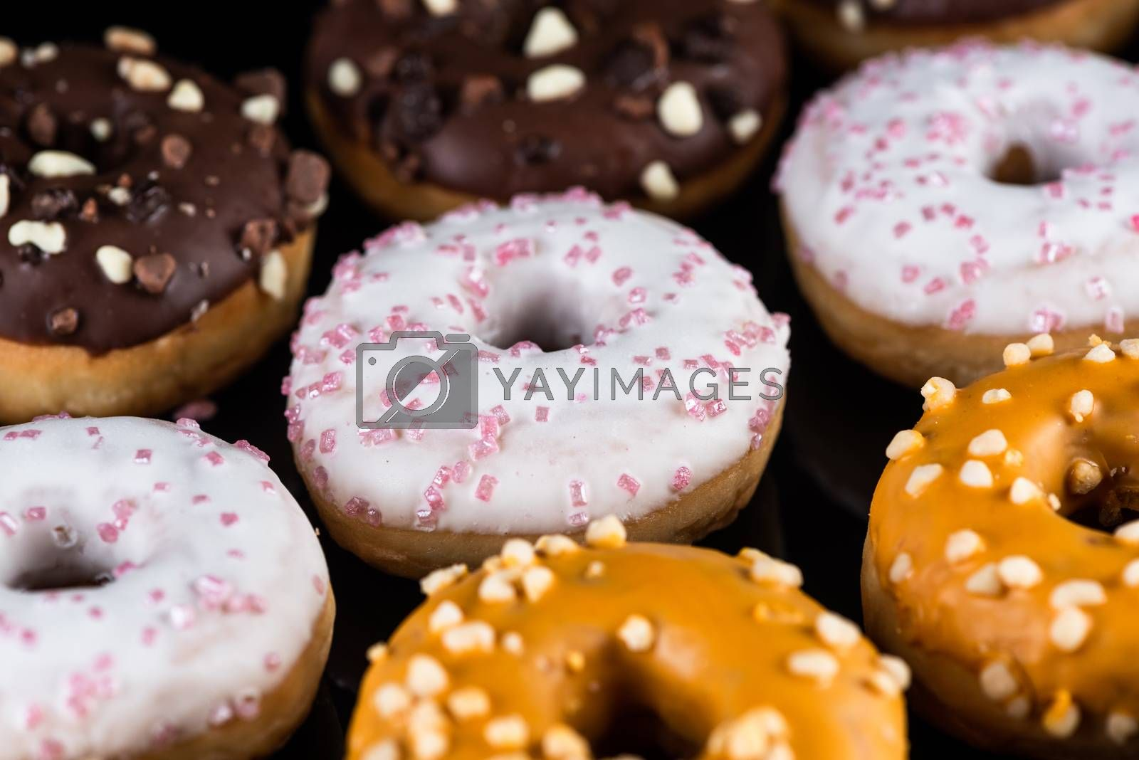 Decorated Donuts or Doughnuts Flat Lay on Dark Background.