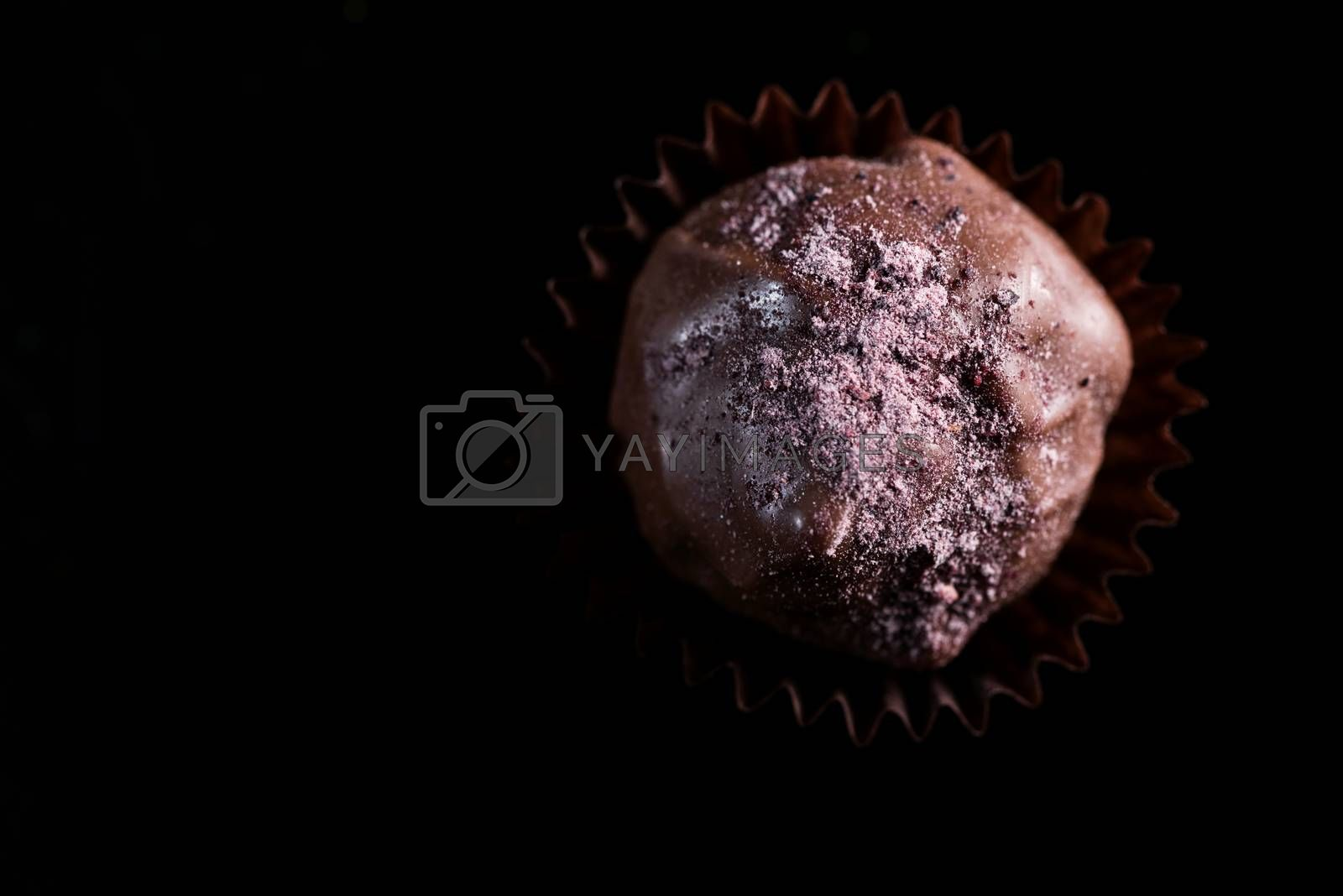 One Single Handmade Chocolate Praline Close Up View. Dark Background with Copy Space.
