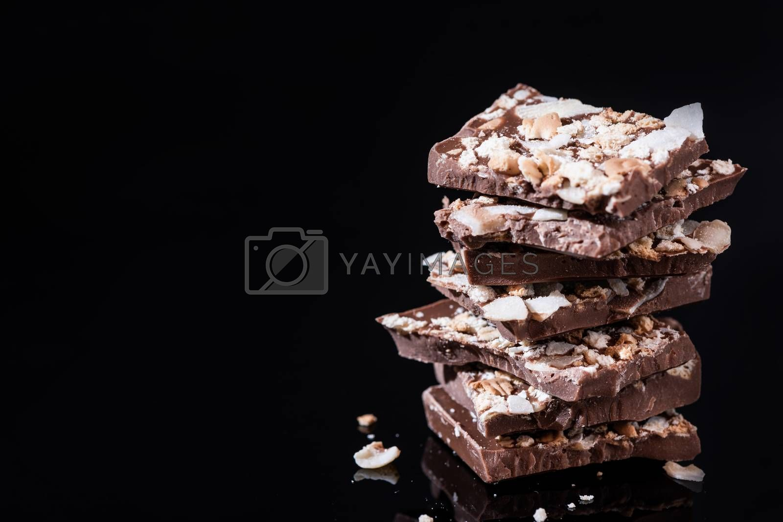 Stack of Broken Chocolate Pieces on Black Background. Copy Space by merc67