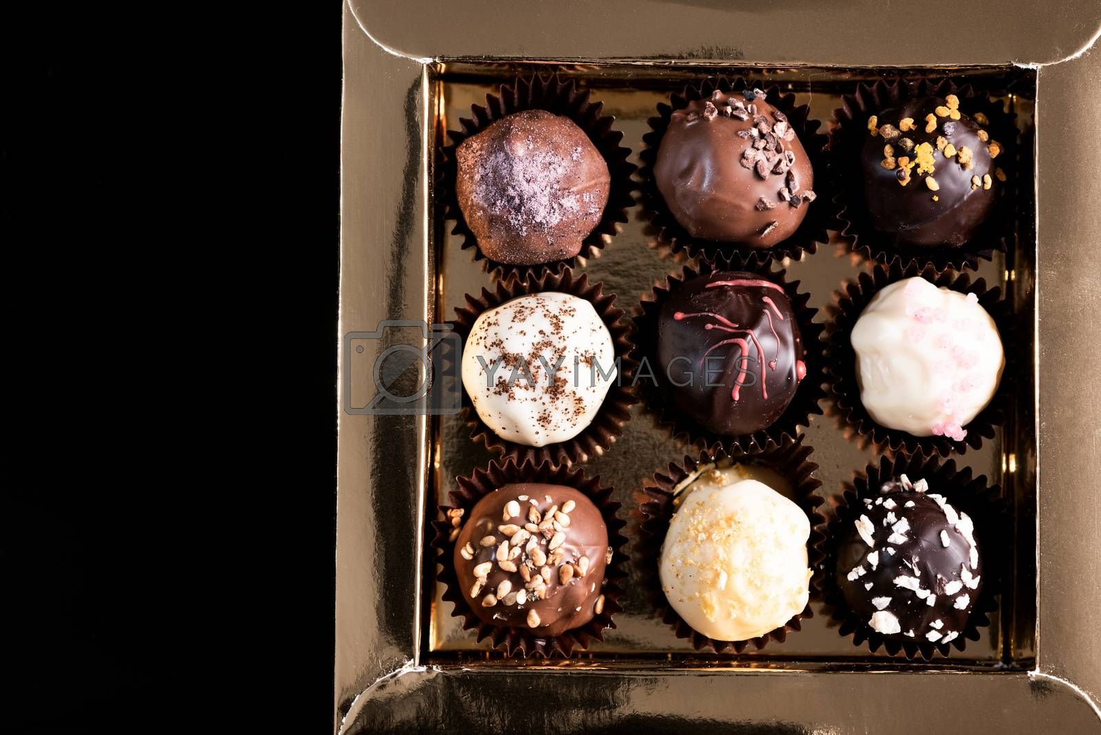 Box with Chocolate Pralines on dark Background. Copy Space.
