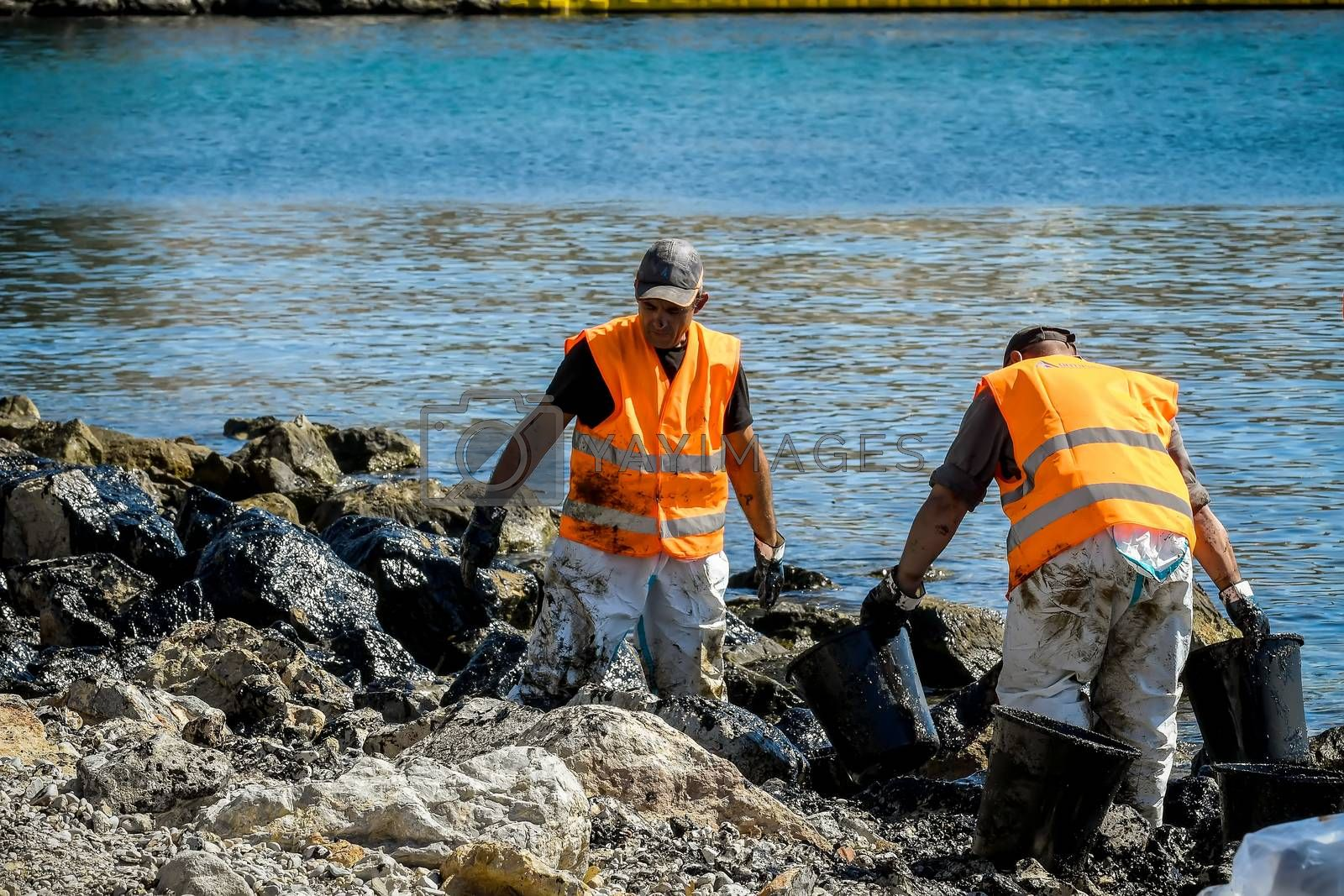 Salamis, Athens, Greece - Sept 13, 2017: Workers try to clean up oil that has washed ashore, on a beach of Salamis island near Athens, after an old tanker sank close to Salamis island
