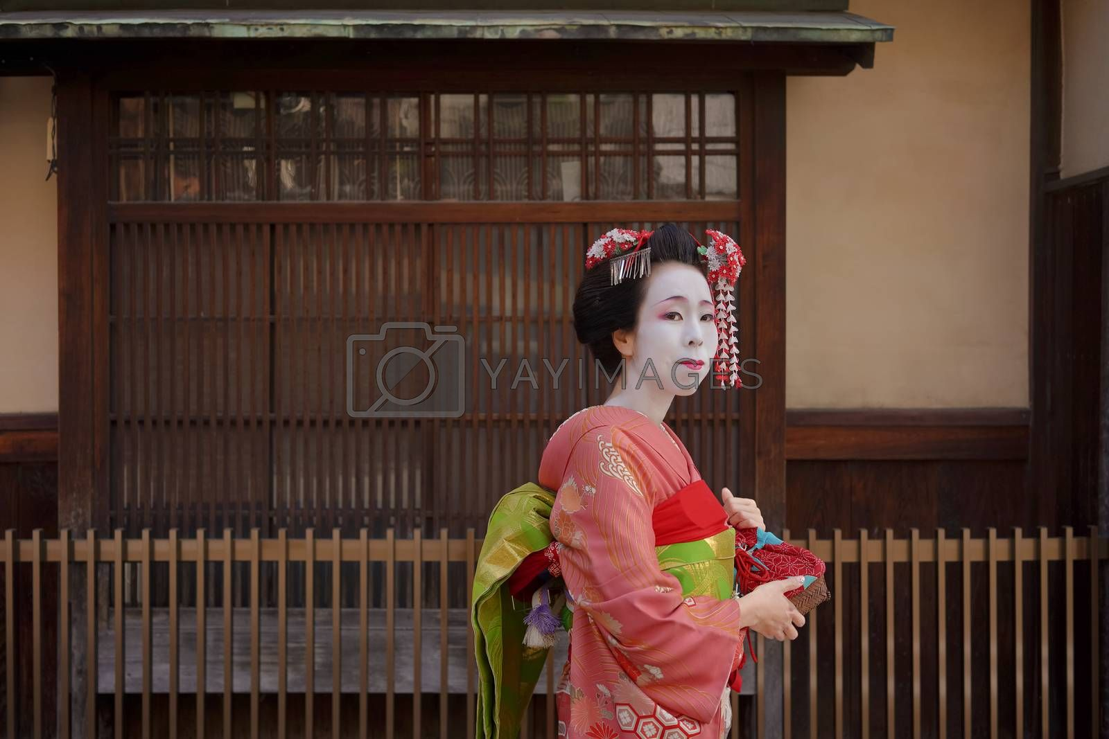 Maiko in a kimono walking in front of the gate of a traditional Japanese house in Kyoto.