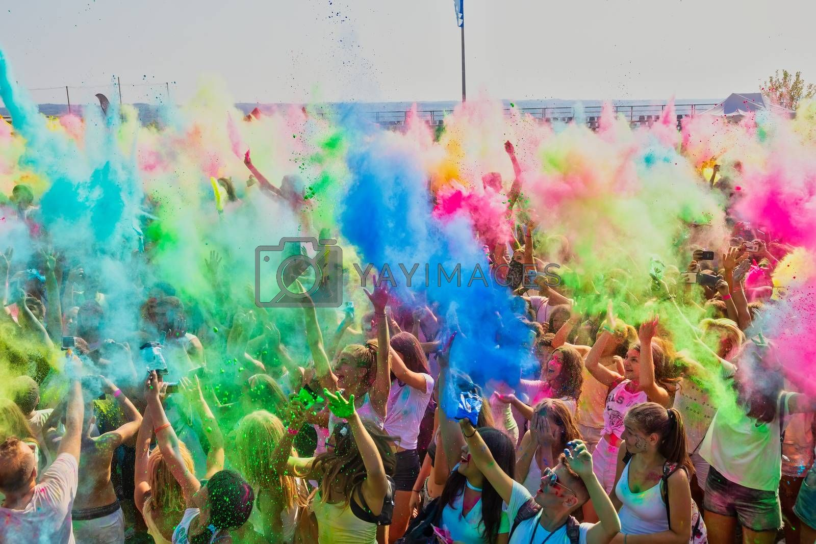 """Thessaloniki, Greece - September 2, 2018: Crowds of unidentified people throw colour powder during the """"Day of Colours"""" annual event."""