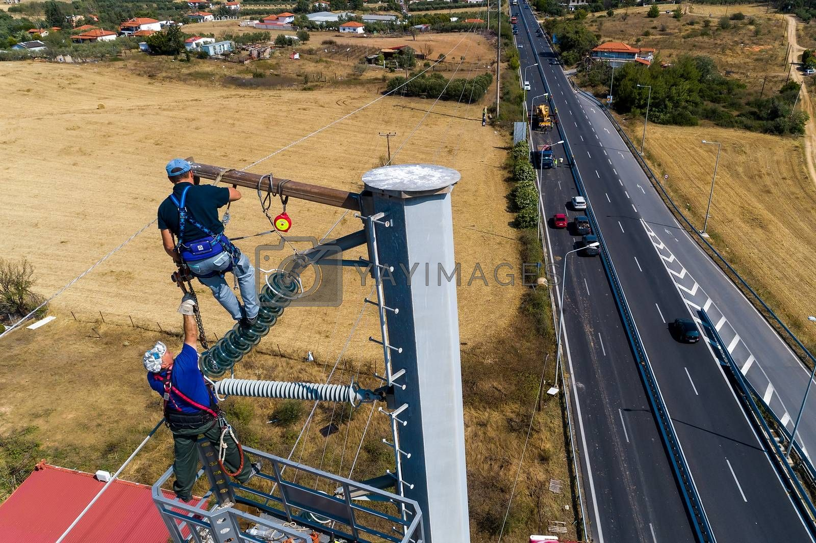 Chalkidiki, Greece - July 12, 2019: Electricians are climbing on electric poles to install and repair power lines after the fierce storm that struck the area