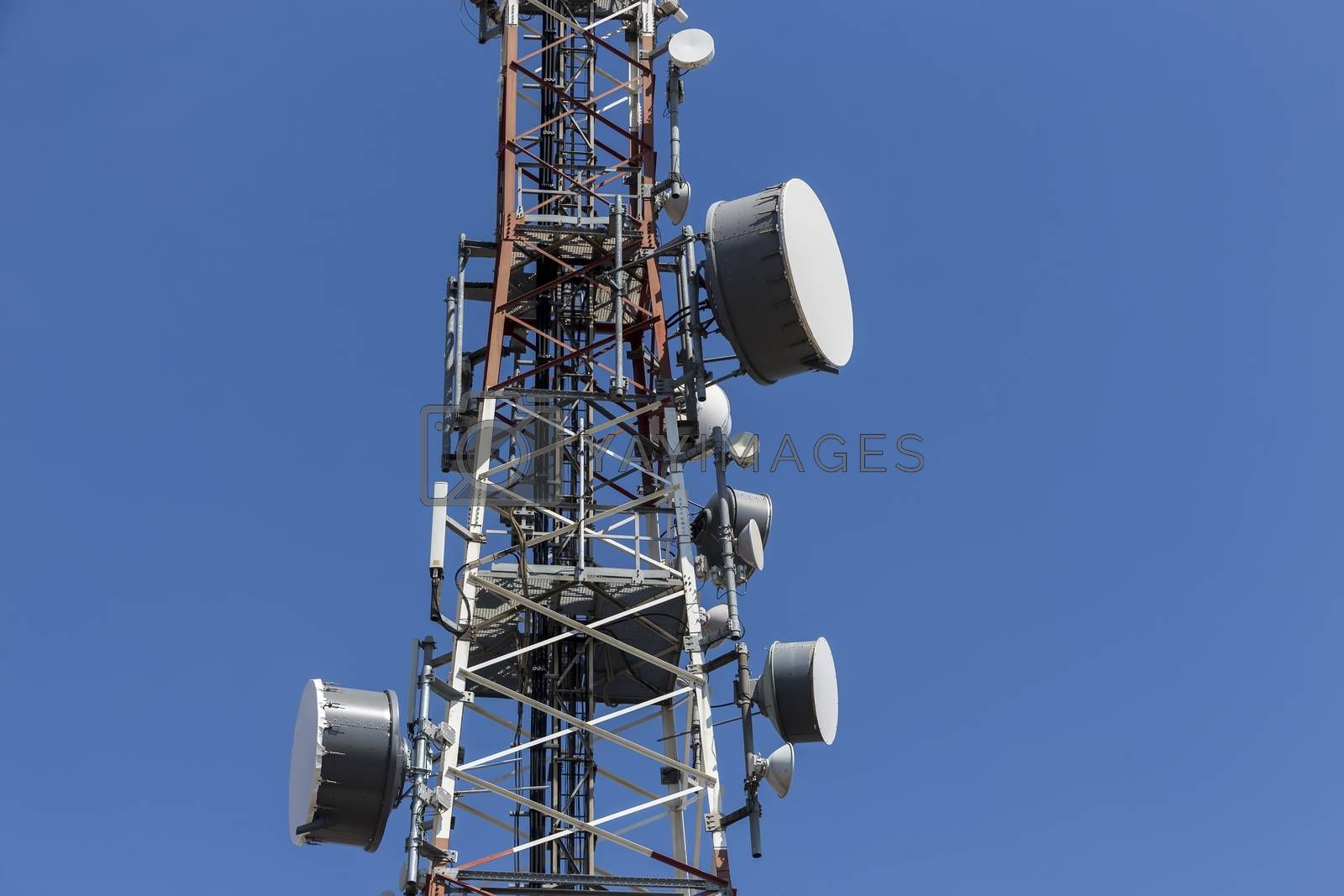 communications tower with antennas against blue sky