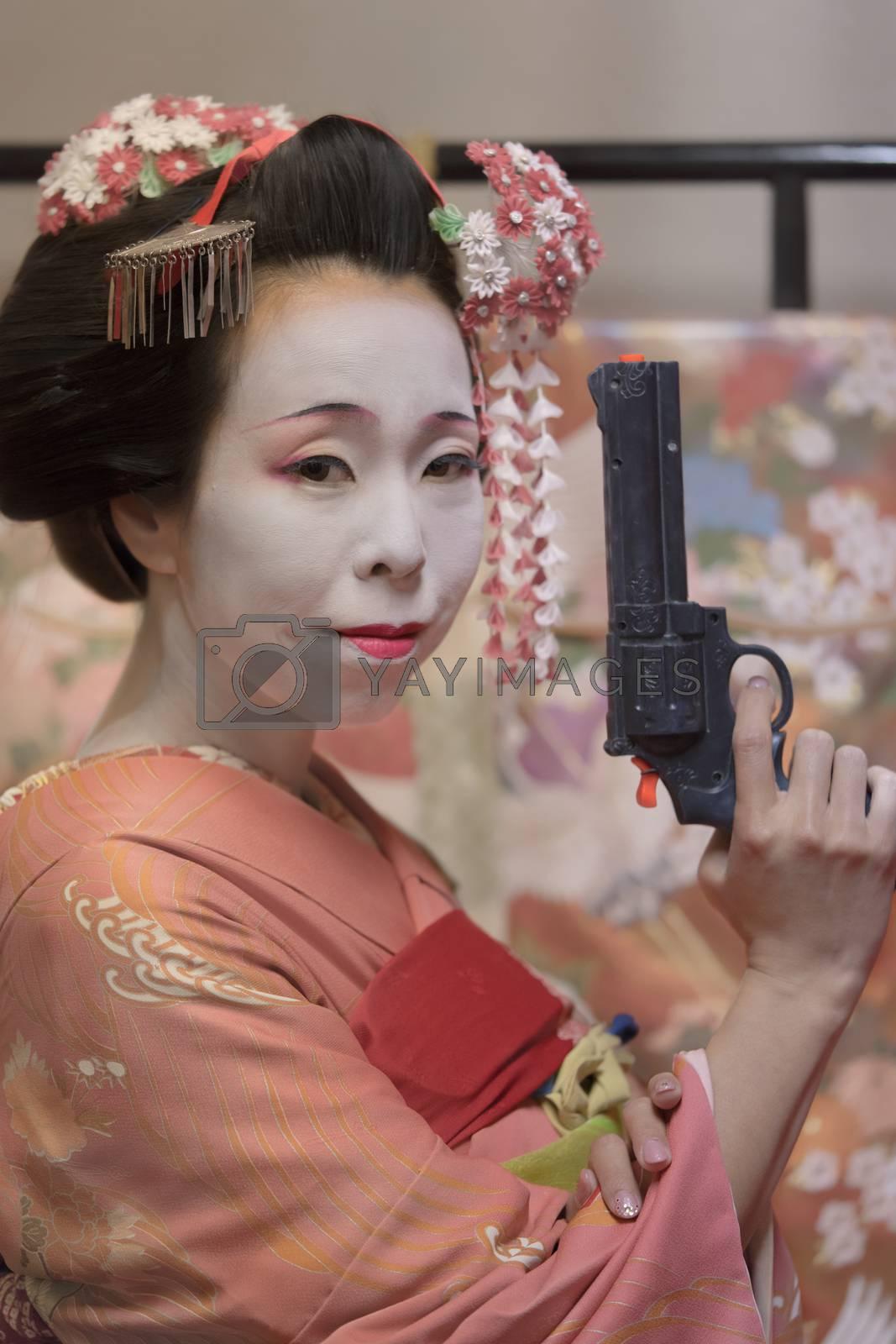 Maiko in kimono holding a plastic gun in her hand.