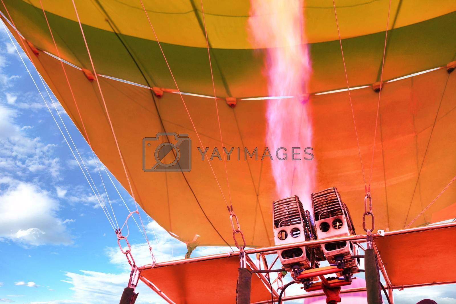 The flame of a powerful gas burner heats up, becomes fiery coral in color and fills the balloon balloon with hot air