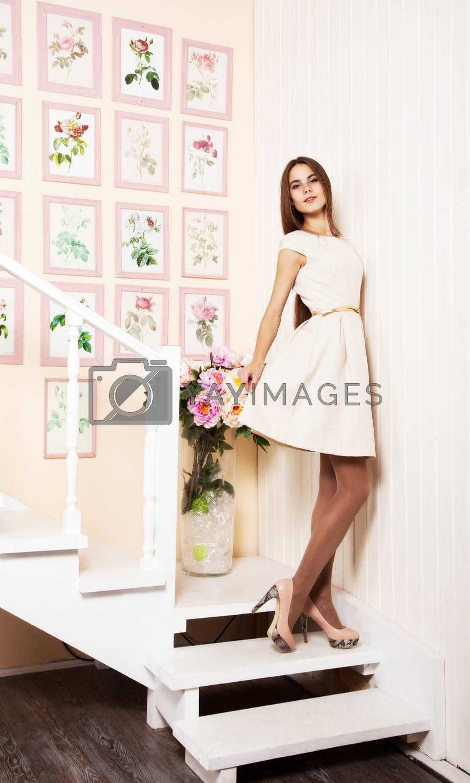 joyful girl in bright dress standing on the stairs indoor