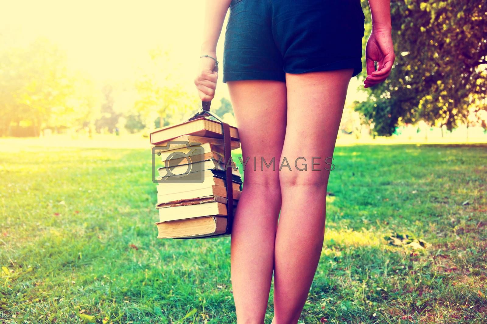Girl holding a stack of books. Education. Back to school. Instagram vintage picture.