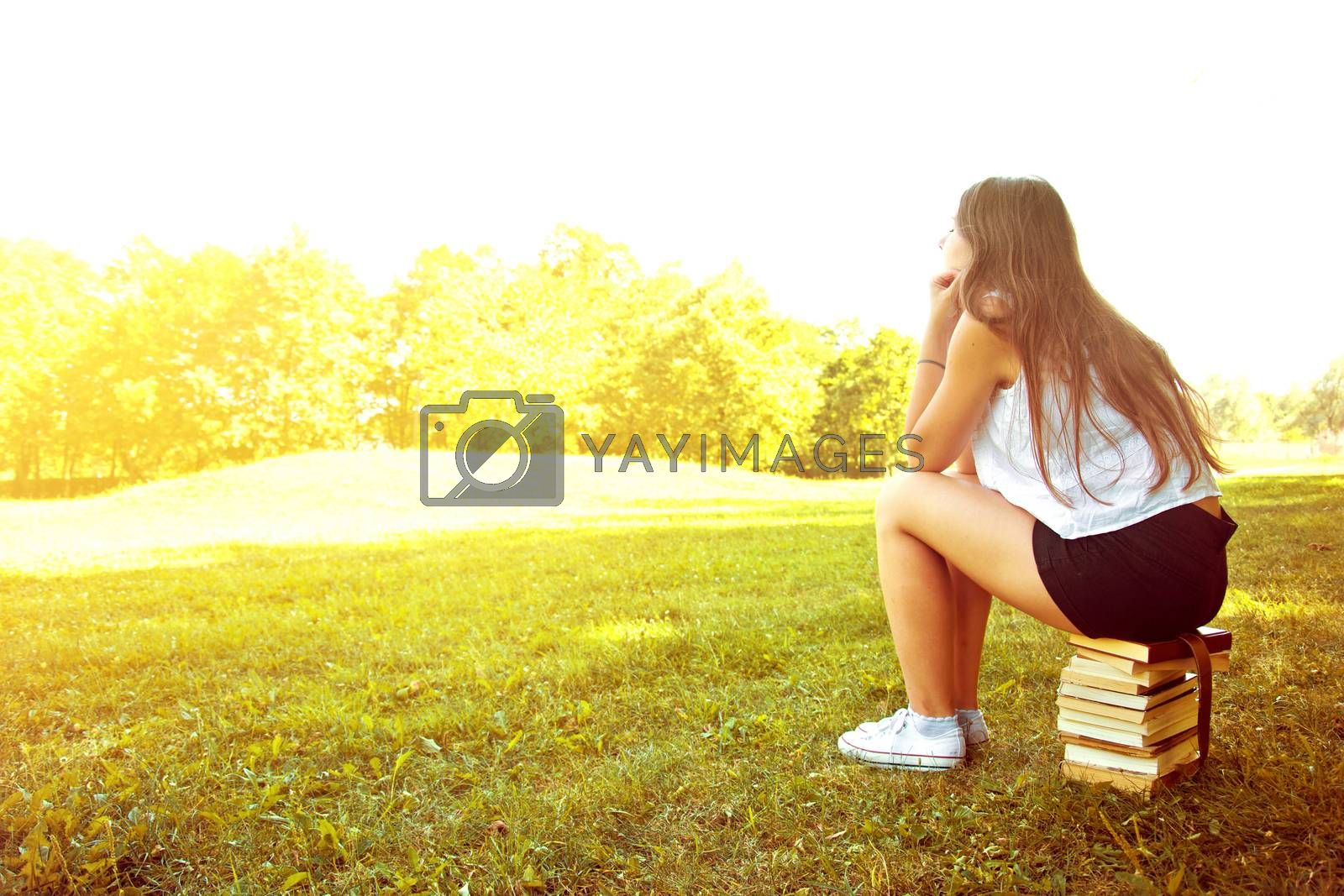 Attractive female college student daydreaming and sitting on the stack of books. Education. Back to school conceptual image.