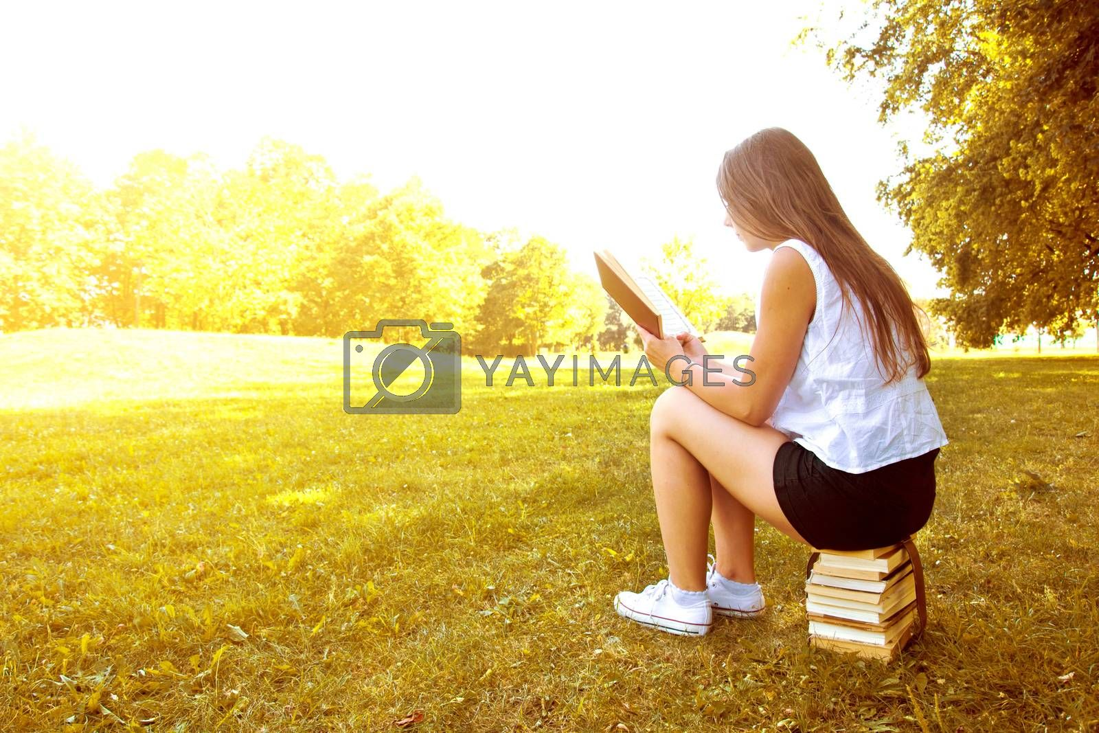 Attractive female college student reading a book and sitting on the stack of books. Education. Back to school conceptual image.