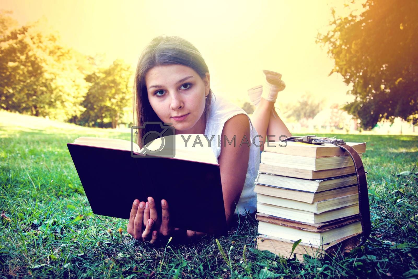 Student girl reading a book on campus grass. Education conceptual image. Instagram vintage picture.
