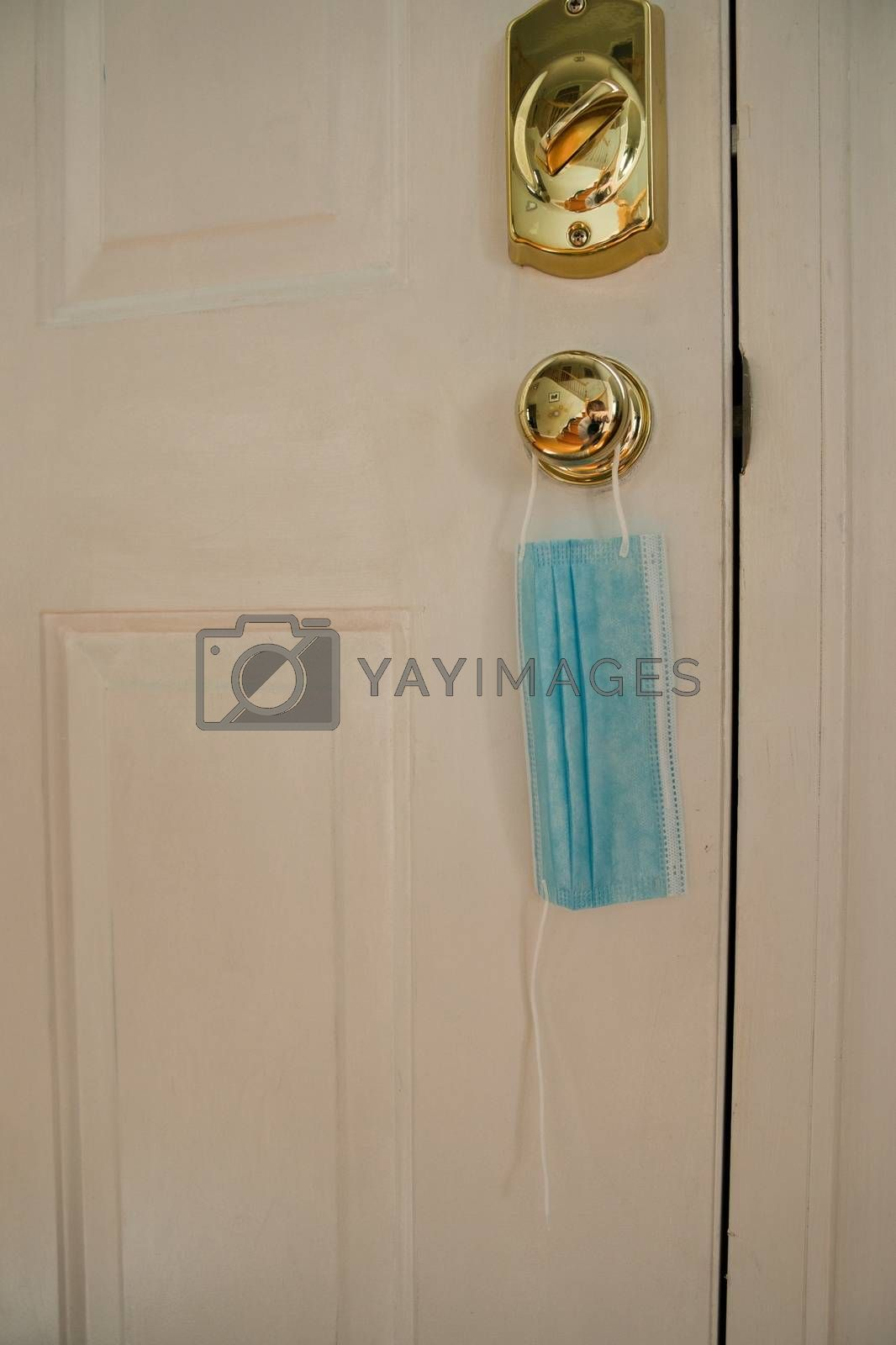 Mask hanging on door with broken string. Indicating an end to coronavirus pandemic. Facemask for protecting during covid-19