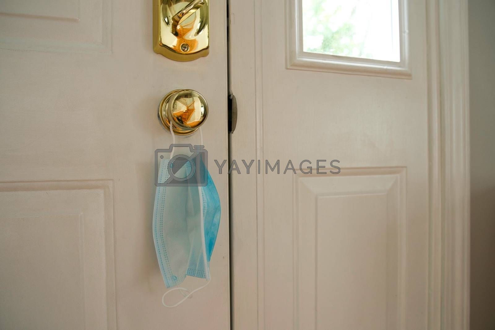 Face mask hanging from door handle on white door with sunlight coming in through window. Covid-19 coronavirus concept image with room for text or copy