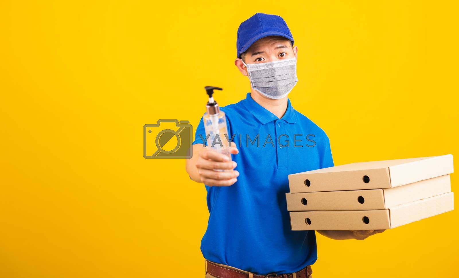 Asian young handsome delivery man wearing face mask protective germ virus holding alcohol sanitizing gel and boxes on hand, studio shot isolated on yellow background, outbreak coronavirus COVID-19