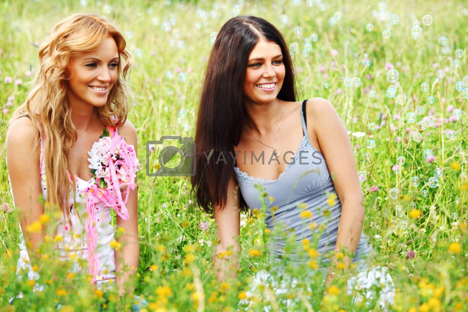 Beautiful girls having fun outdoors, girlfriends on green grass field in soap bubbles