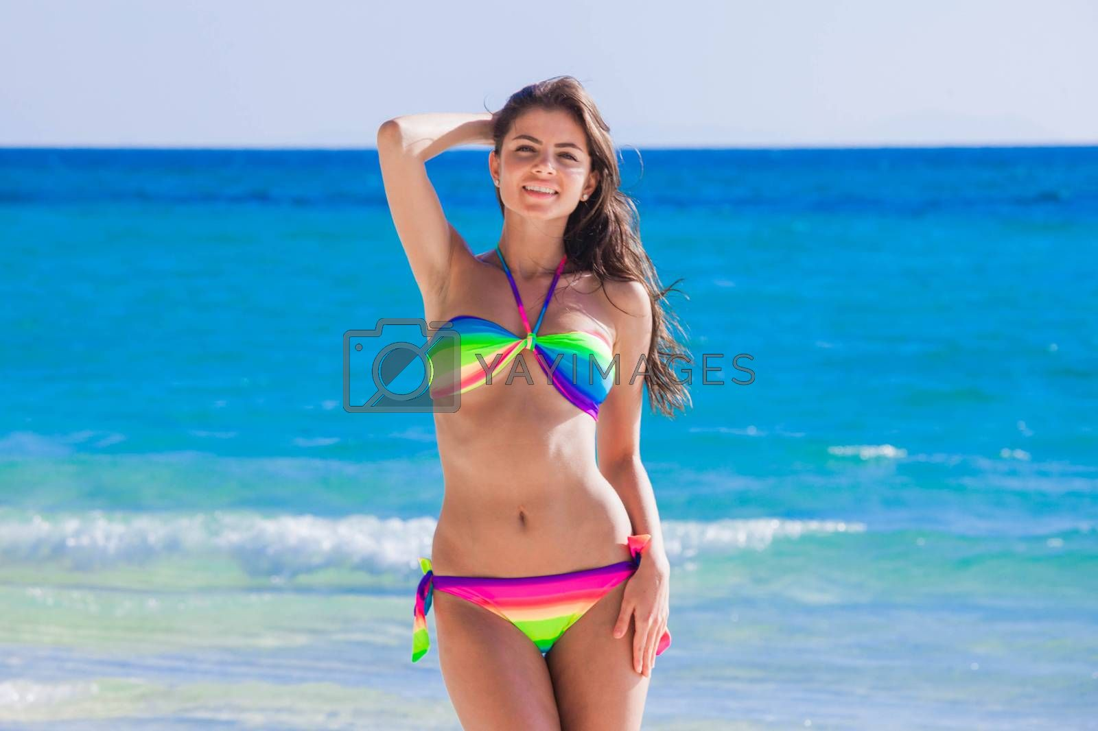 Happy tanned girl in rainbow bikini at seaside, blue sea water on background