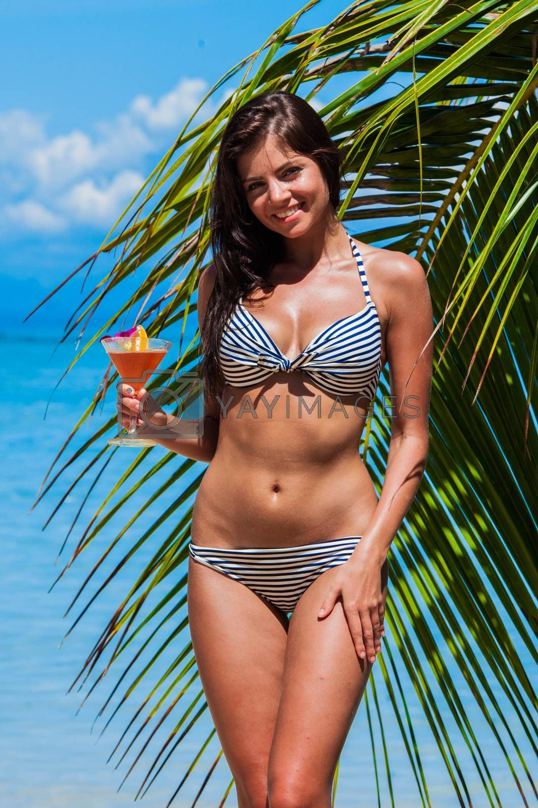 Happy smiling girl in bikini with cocktail on beach in Thailand