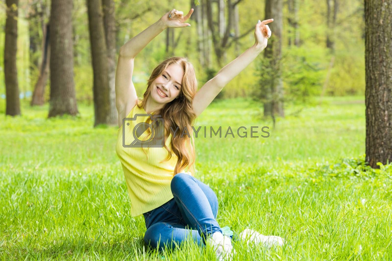 Young attractive woman relaxing in nature , stretching raised arms sitting in park on spring grass