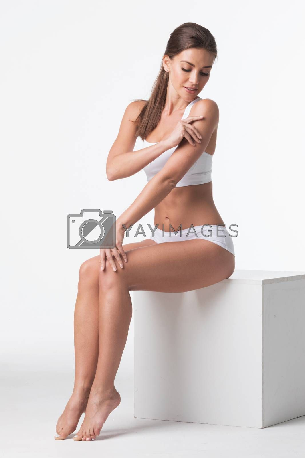Young beautiful woman in cotton underwear touching own skin sitting on a cube on white background