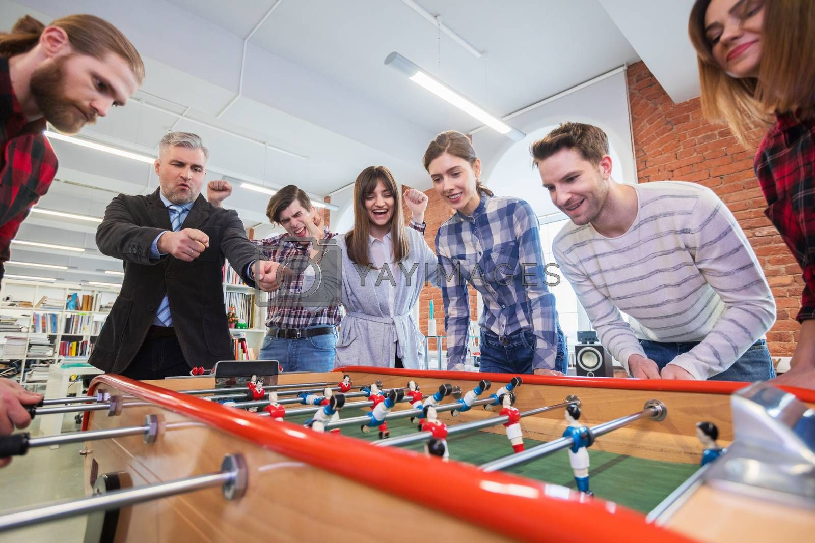 Business people having great time together, colleagues playing table football in modern office