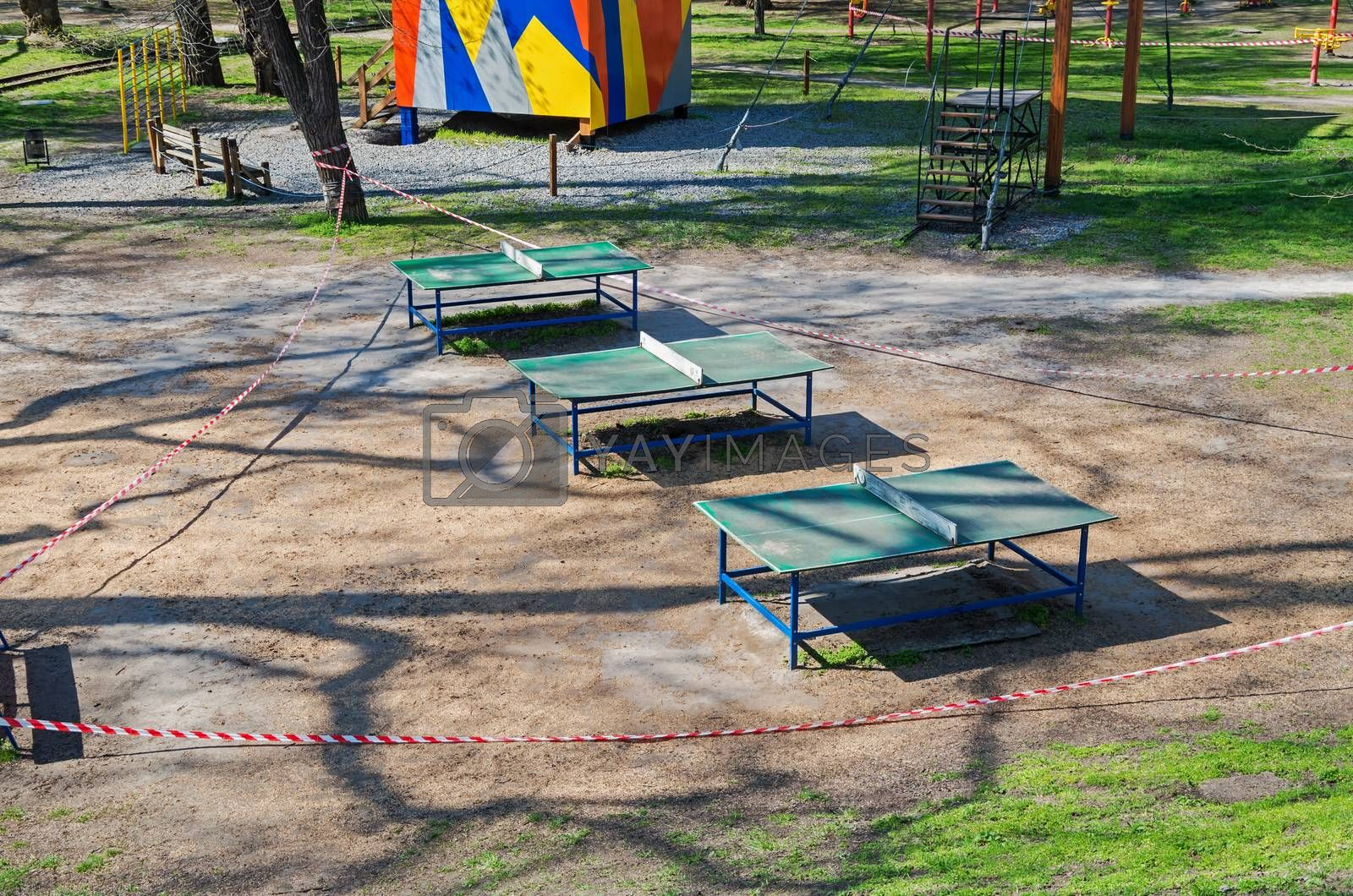 Sports playground with tennis tables in old city park is fenced with barricade tape during COVID-19 coronavirus infection pandemic. It is forbidden to be in public places during quarantine