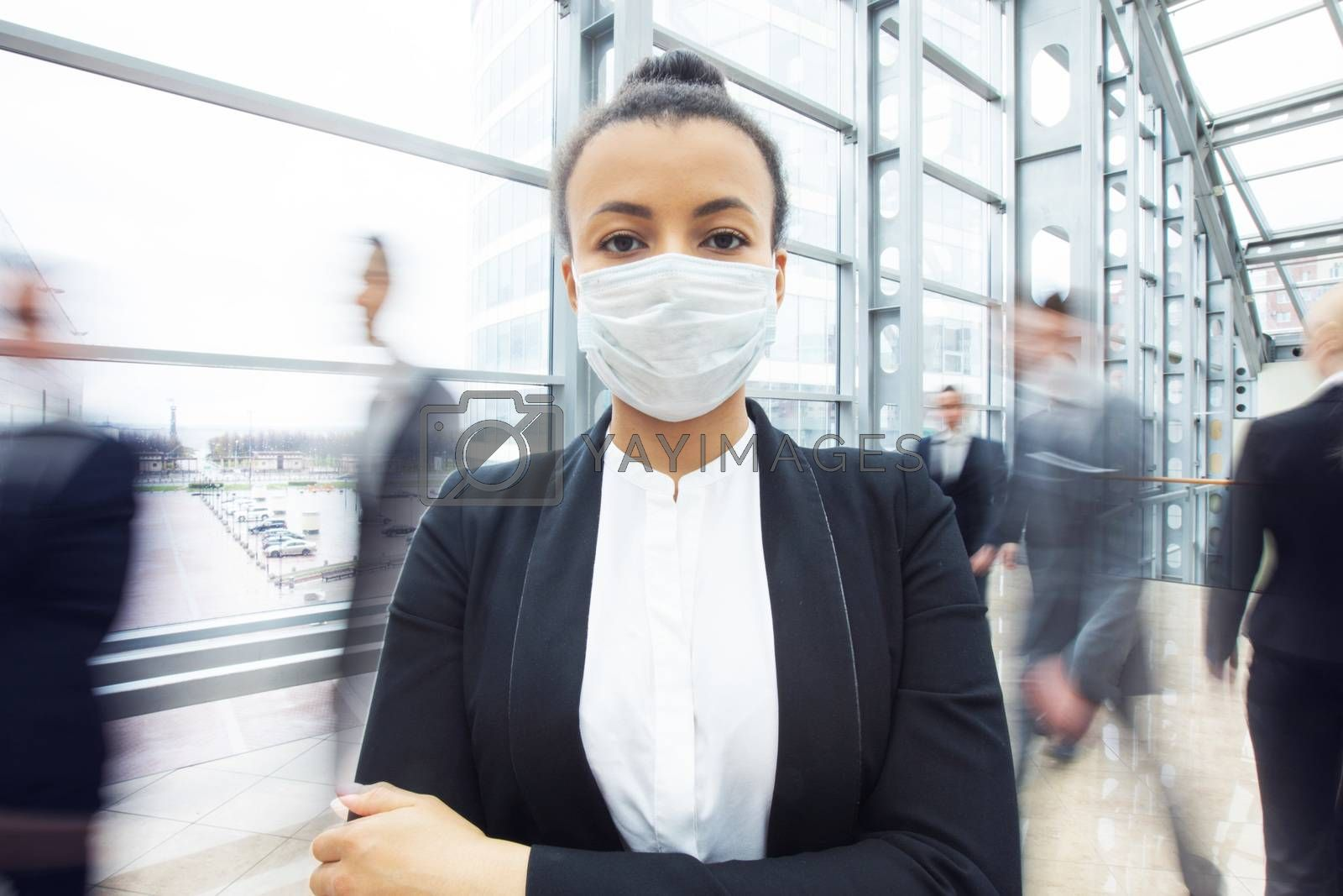 Beautiful african business woman in suit wearing surgical protect mask standing in a crowd of walking people. Concept for prevent for coronavirus outbreak