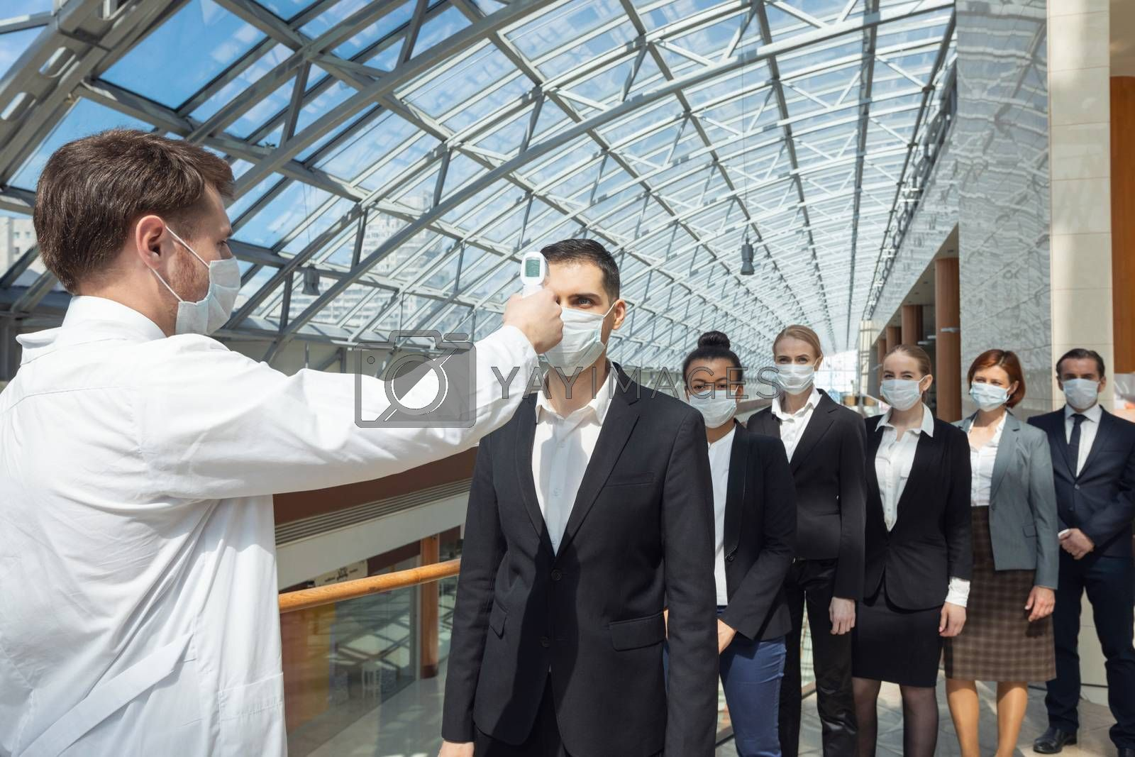 Doctor check body temperature of business team by ALotOfPeople