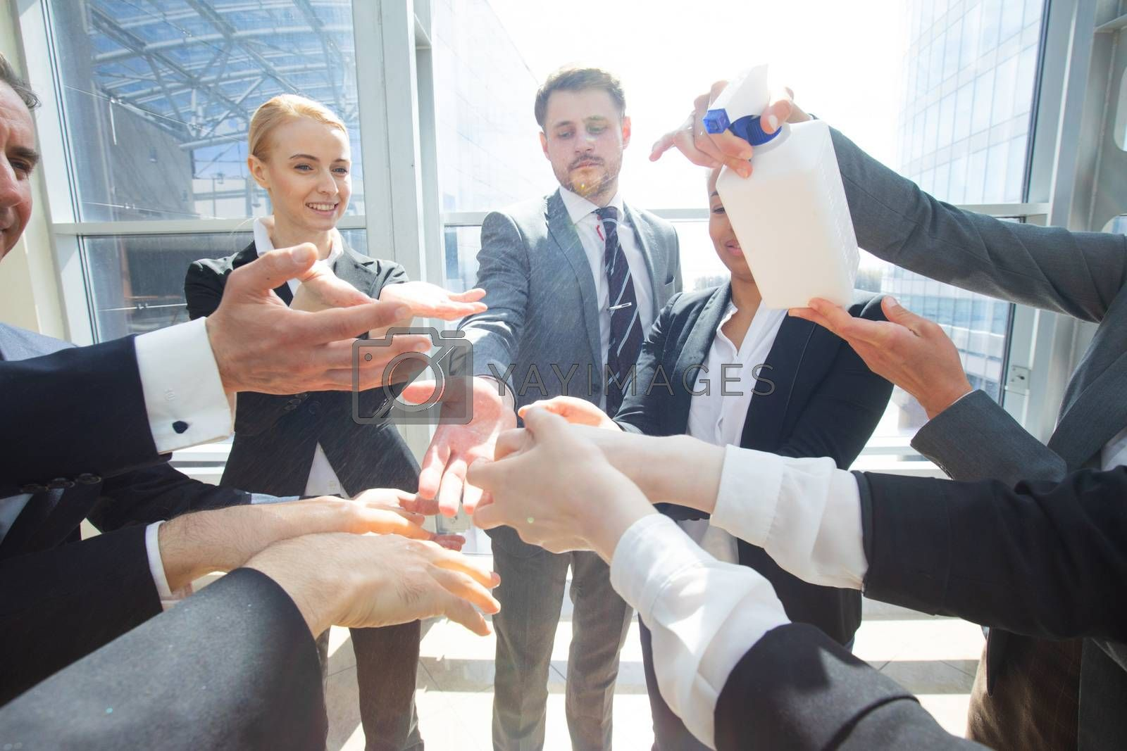 Business people using hand sanitizer by ALotOfPeople