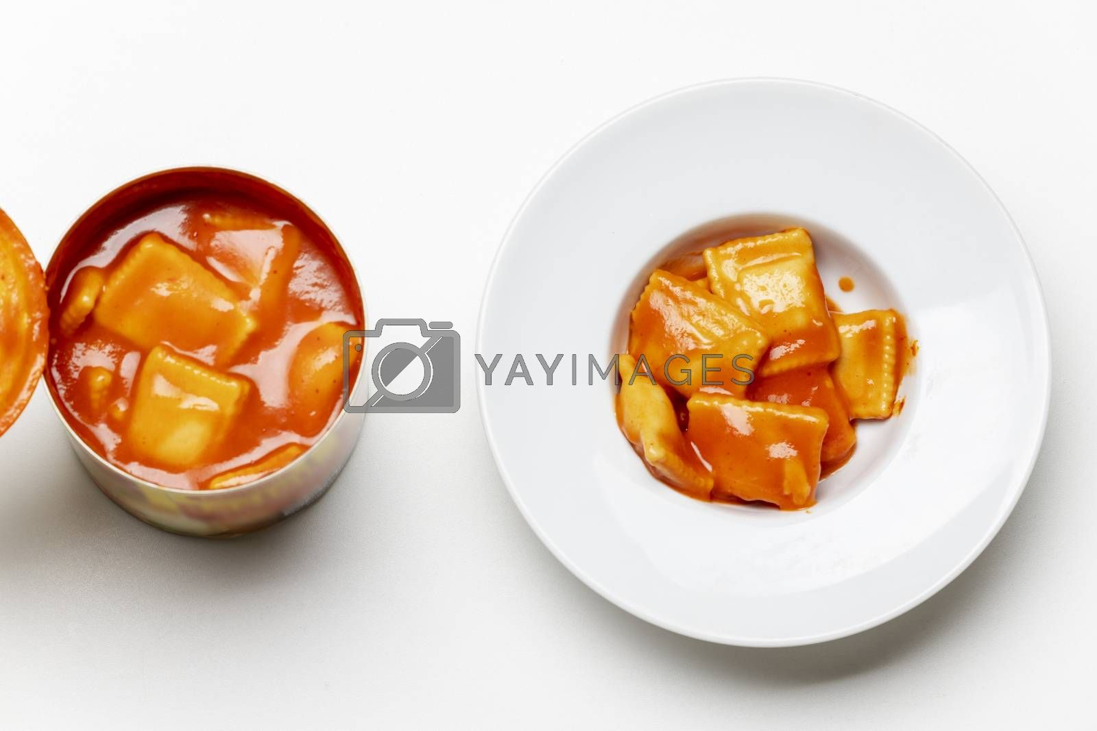 open can of ravioli on white background