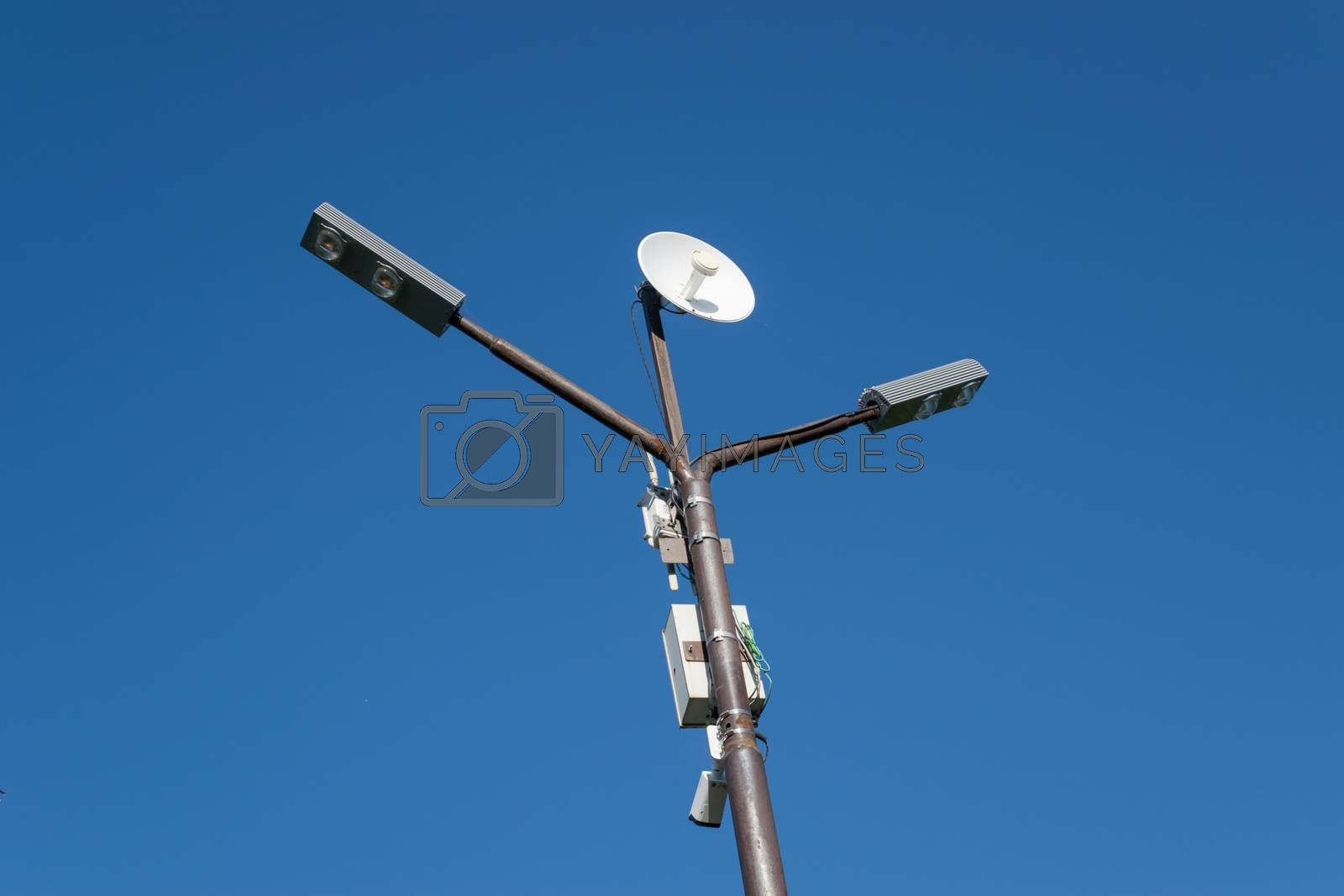 Lamppost with an antenna mounted on it. Pillar against the blue sky.