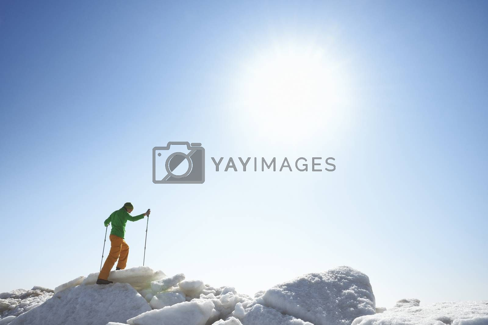 Young adult man outdoors with walking sticks exploring icy landscape