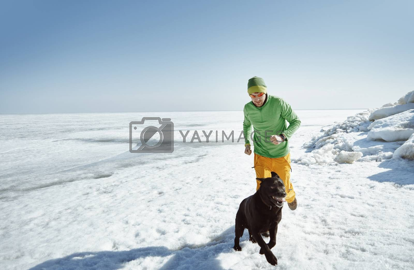Young adult man outdoors with his dog having fun in winter lands by Novic