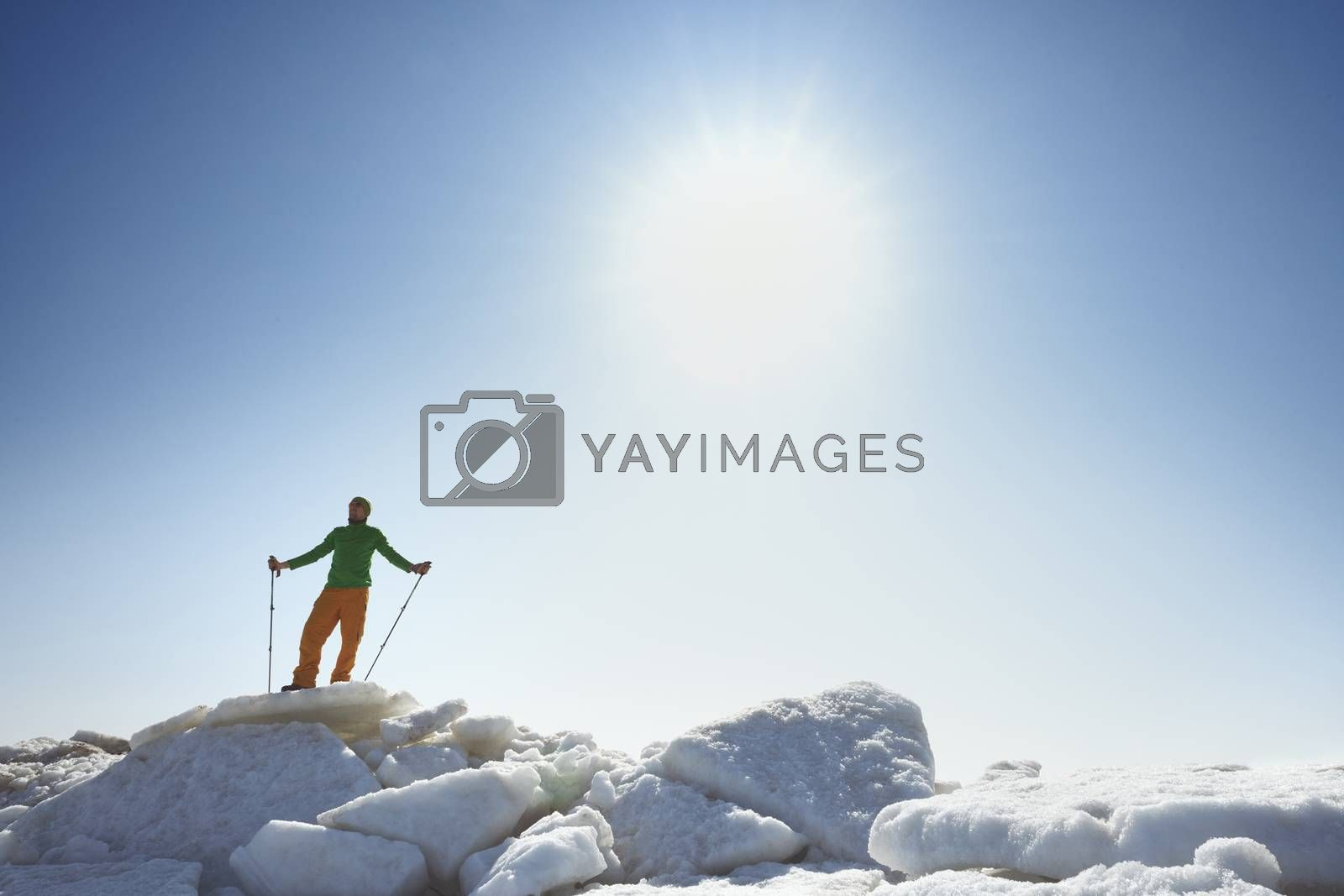 Young adult man outdoors with walking sticks exploring icy lands by Novic