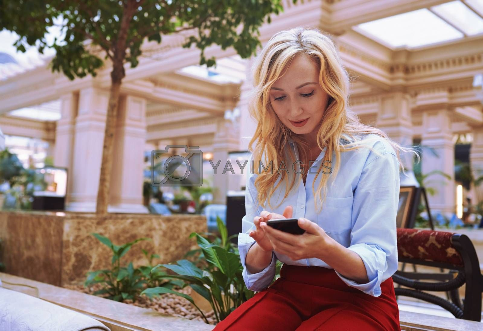 Businesswoman using smartphone in the modern bank lobby by Novic