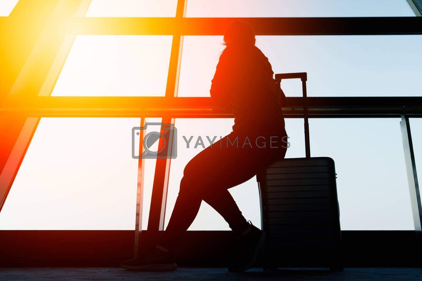 woman sitting on travel luggage looking outside window missing home