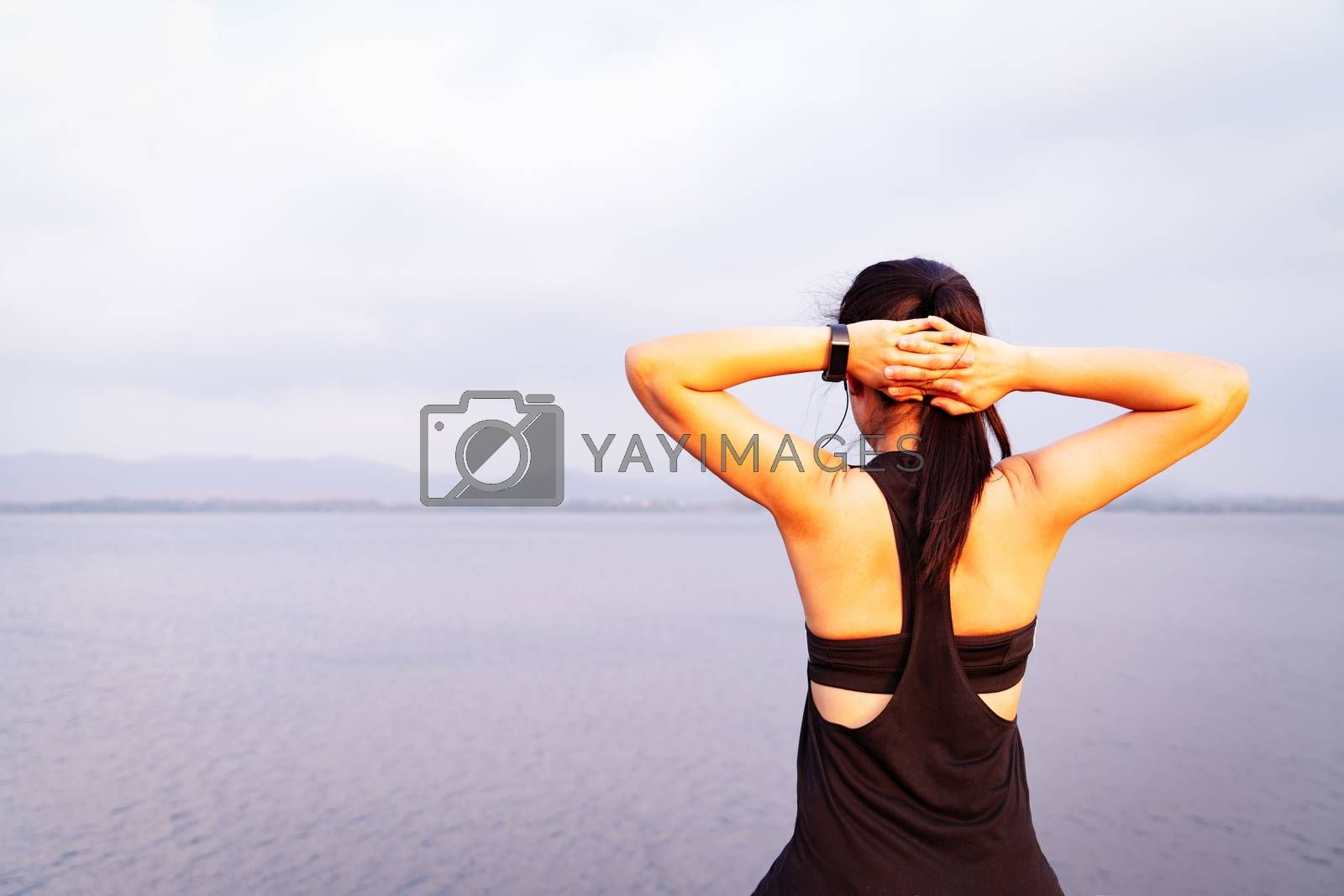 Young athlete woman streching near the lake outdoor, asian Fitness walking and exercise in sunset scene. wellness and sport concepts