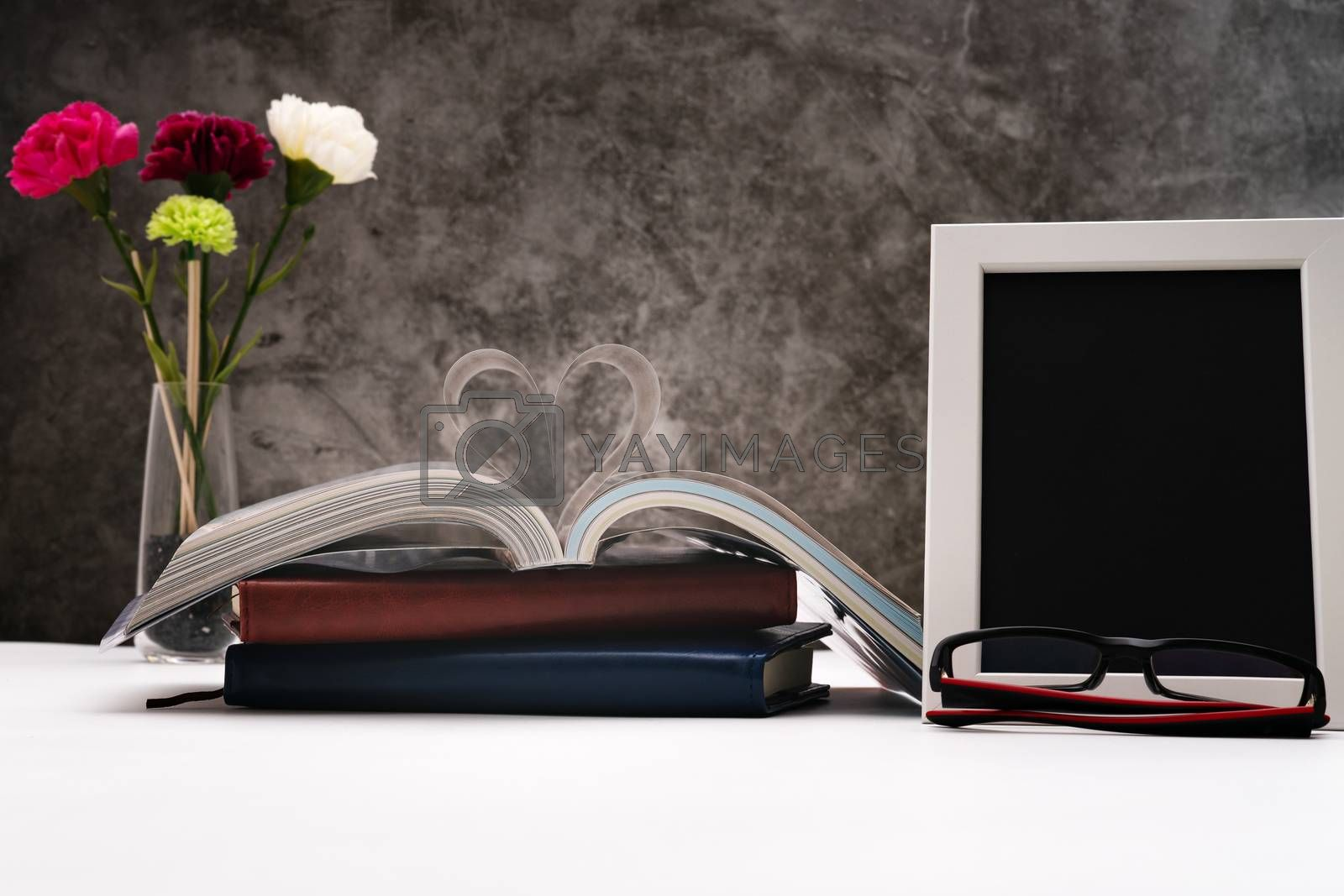 Love story book with open page of literature in heart shape and photo frame for writing space